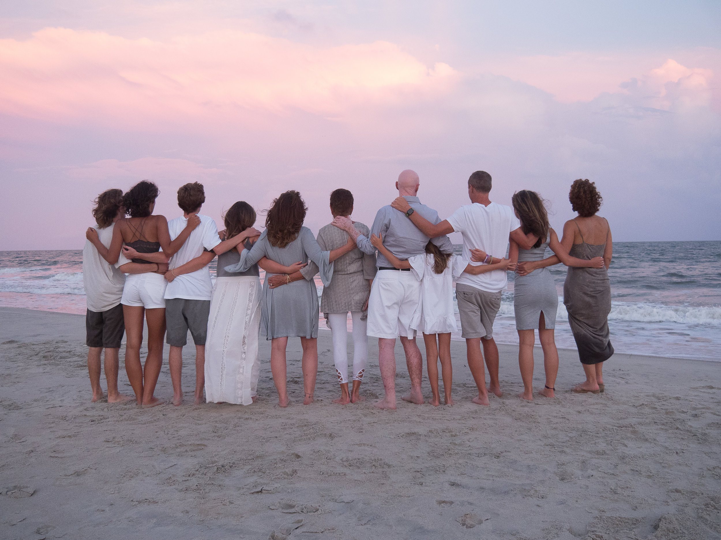 - Family with arms wrapped around each other looking out at the ocean at nautical twilight. Ocean Isle Beach, NC.