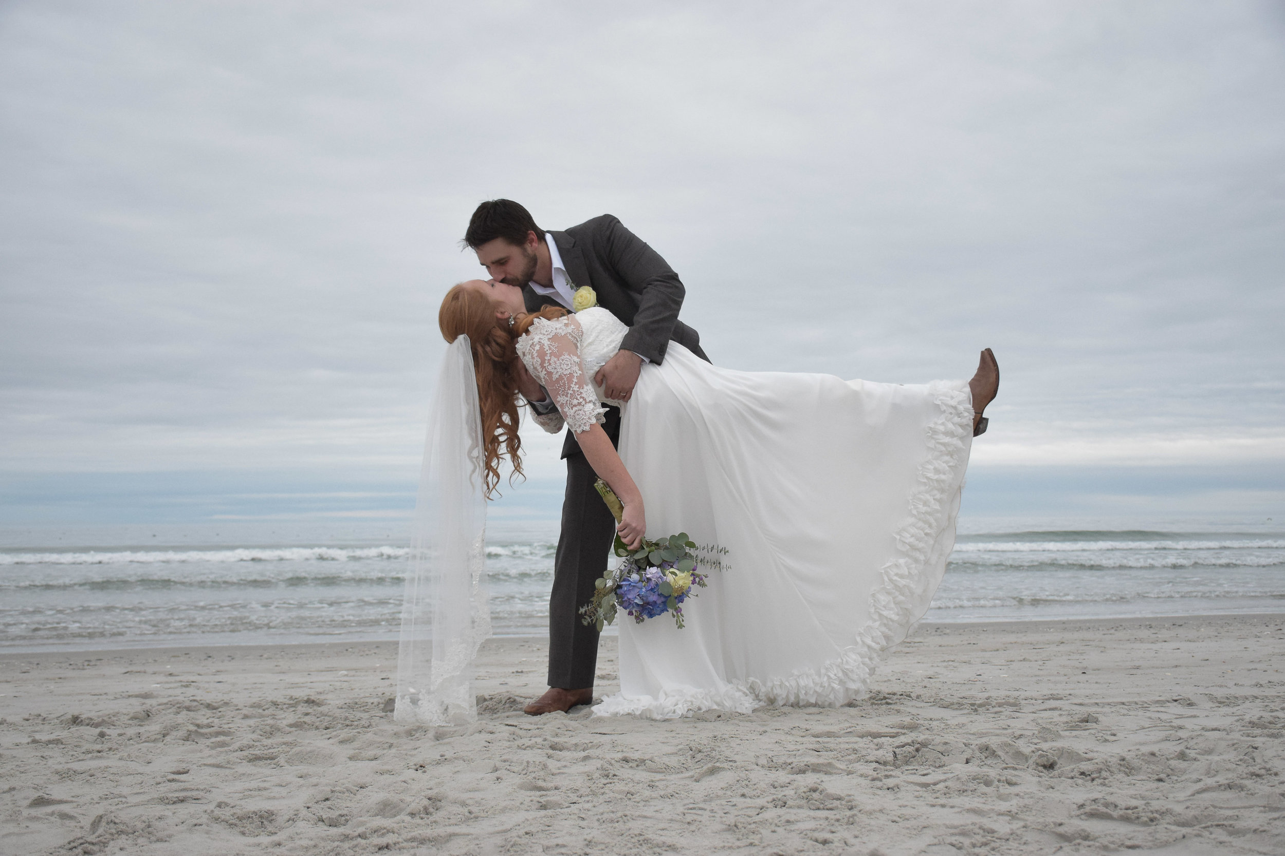 - Groom dipping bride on the beach. January Wedding. Wrightsville Beach, NC.