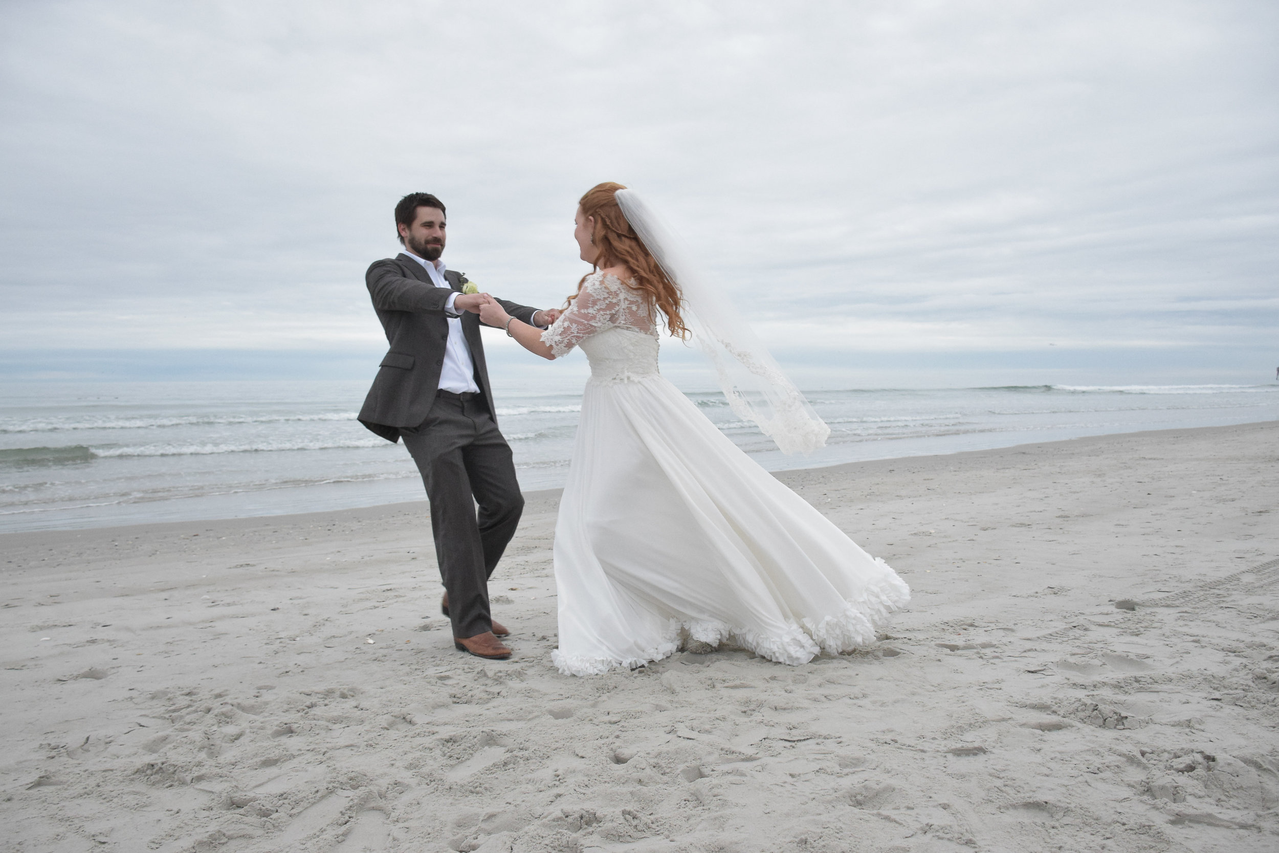 - Bride and groom spinning on a January beach to warm up. Ocean in the background. Wrightsville Beach, NC.