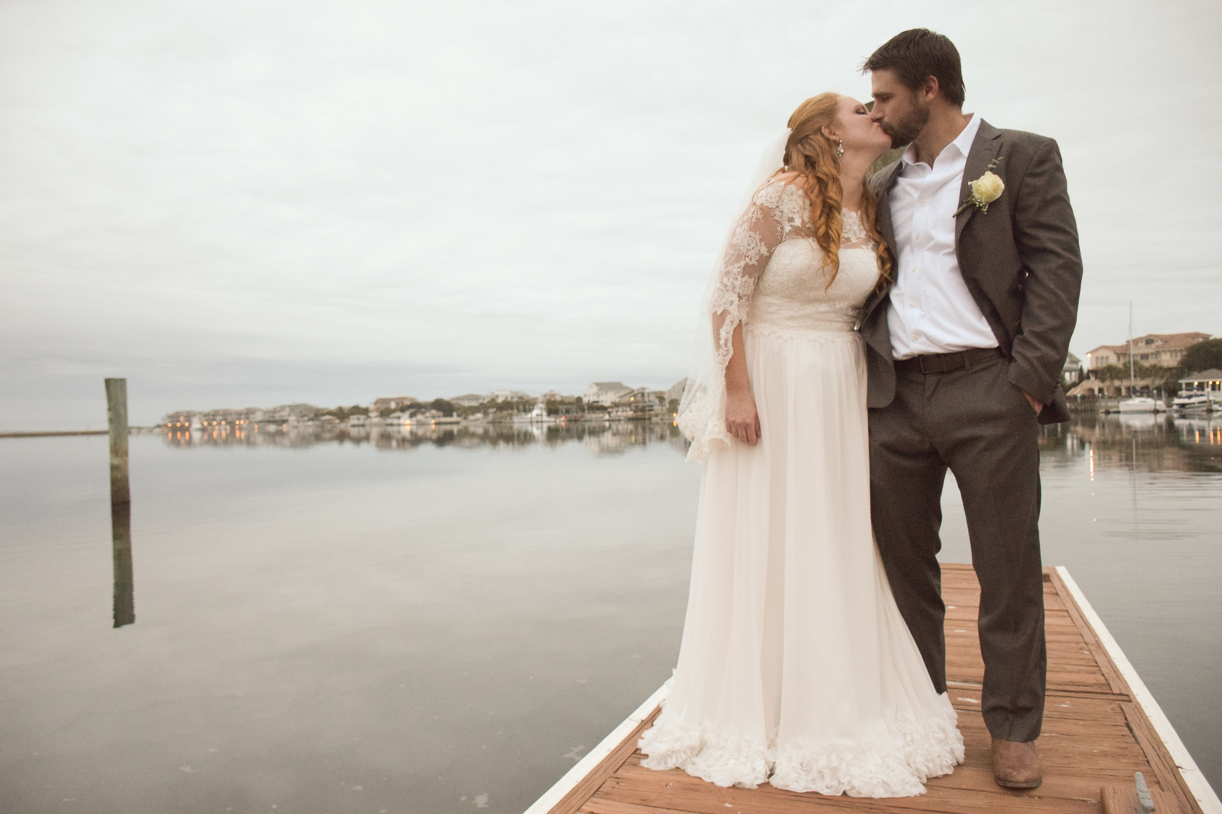 - Bride and groom sharing a kiss on a pier at Wrightsville Beach, NC. Ocean and beach houses in background.