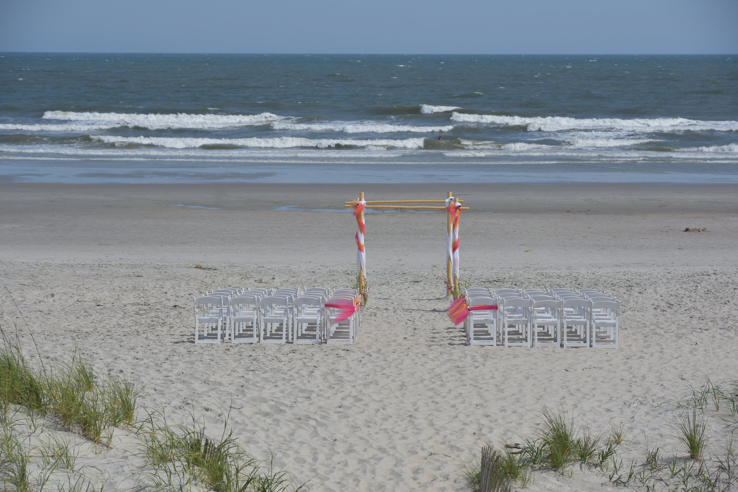 - Small setup for a beach wedding in Ocean Isle NC. Chairs and bamboo arbor facing the beach.