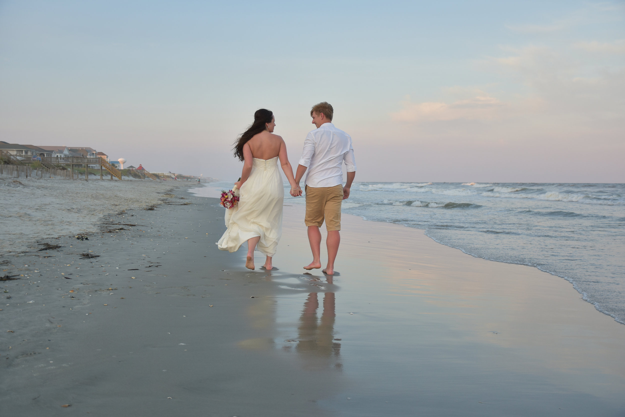- Bride and Groom walking down the beach holding hands at Ocean Isle Beach, NC. Bride is holding bouquet. Picture taken during nautical twilight.