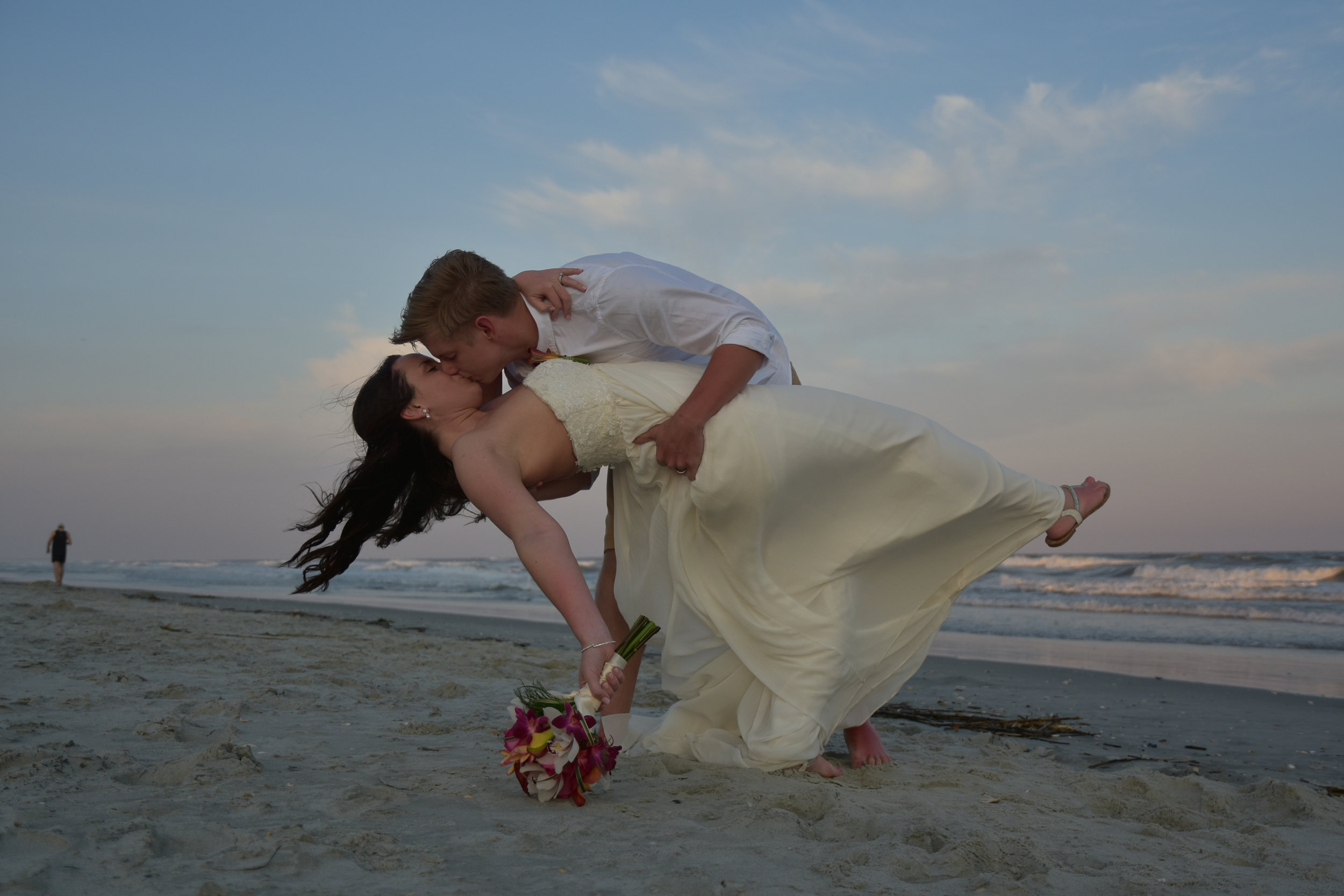 - Groom dipping bride on Ocean Isle Beach, NC. Bride holding bouquet, Billy Beach Photography.