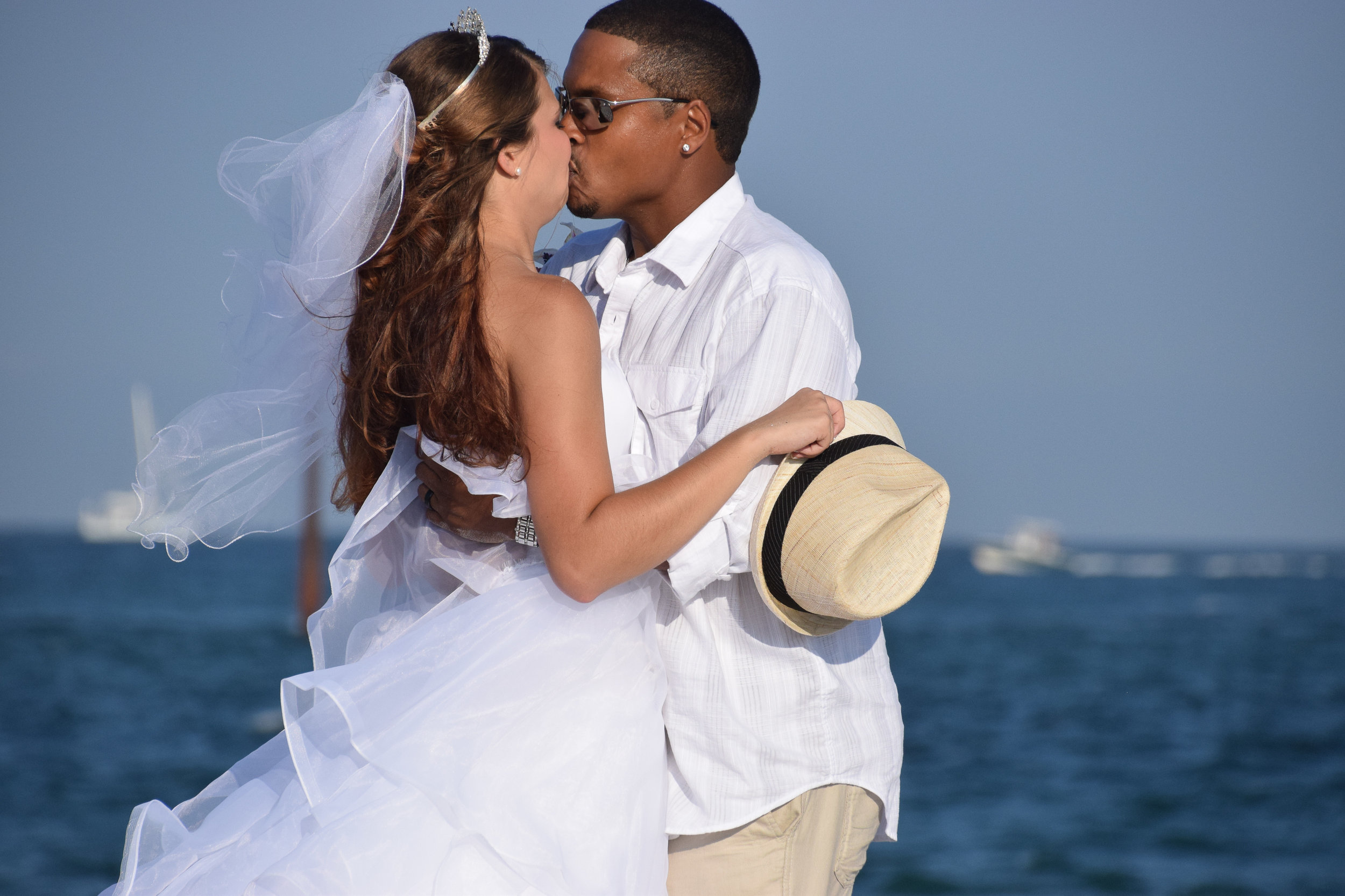 - Newly married bride and groom kissing at access #43 on Wrightsville Beach, NC.Bride holding grooms hat with ocean in the background. Billy Beach Photography.
