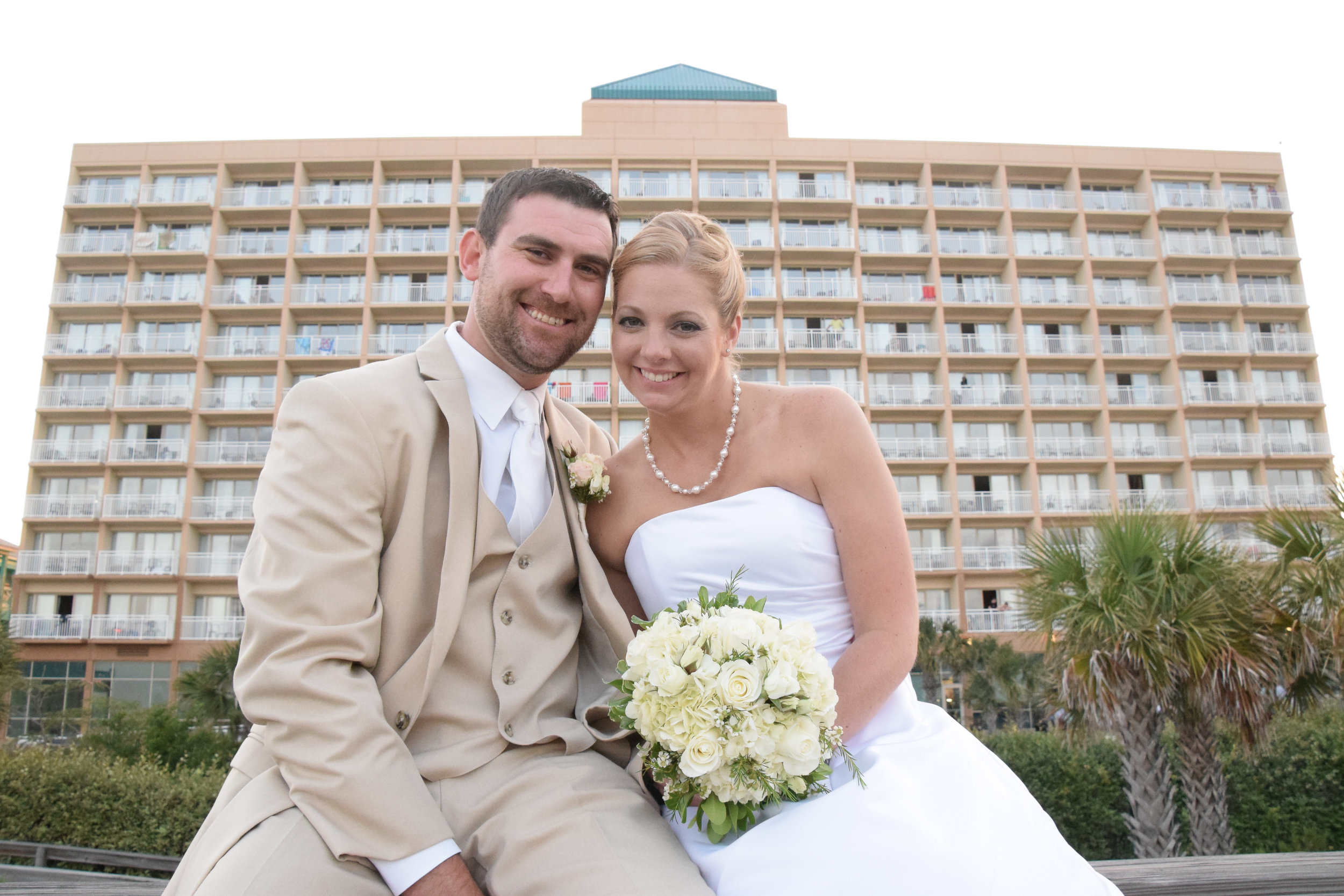 - Bride and groom posing after their wedding ceremony, sitting on a rail in front of the backside of the Courtyard Marriott in Carolina Beach, NC. Billy Beach Photography.
