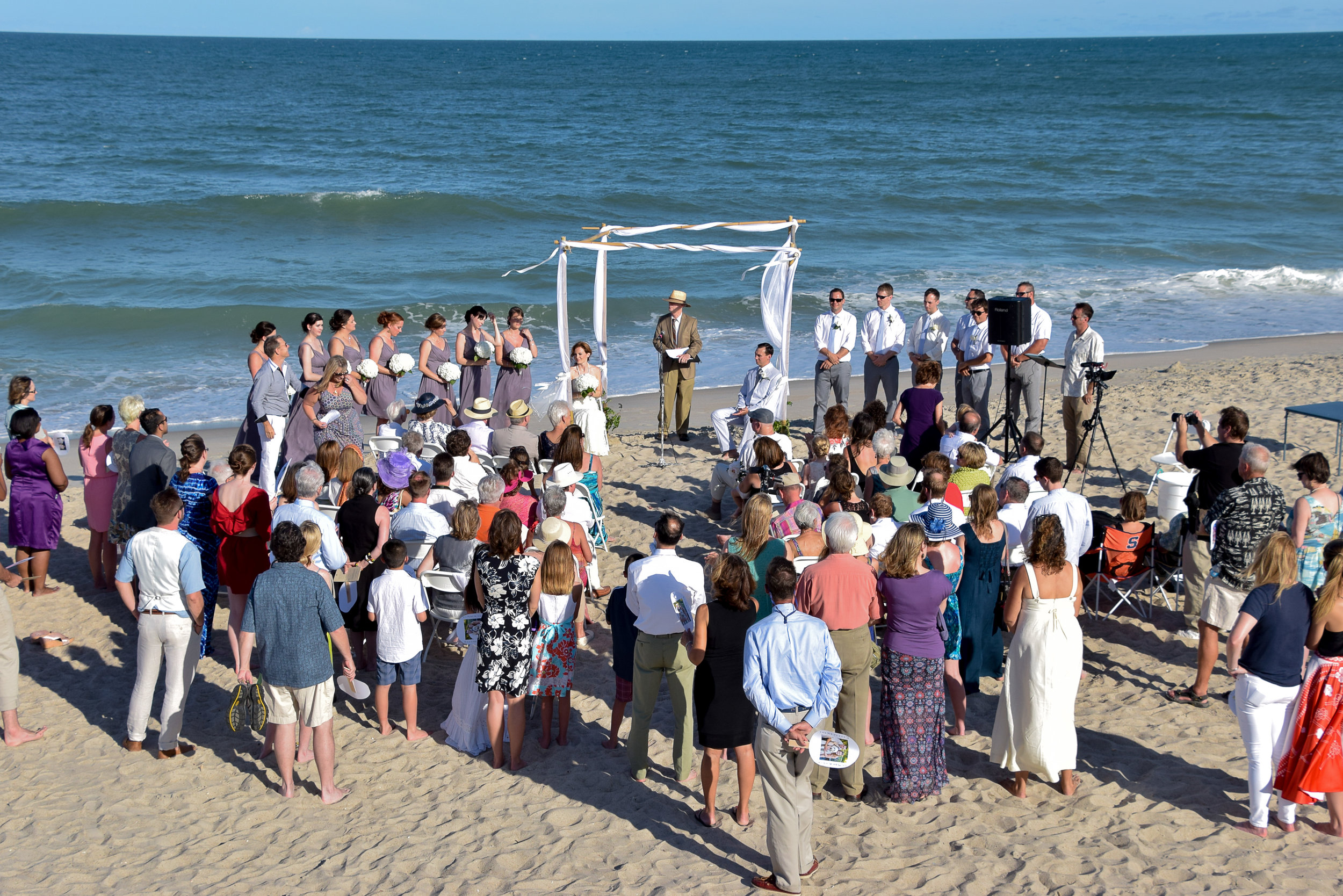 - Wedding Ceremony in progress on Carolina Beach, NC. Ocean in the background. Billy Beach Photography.
