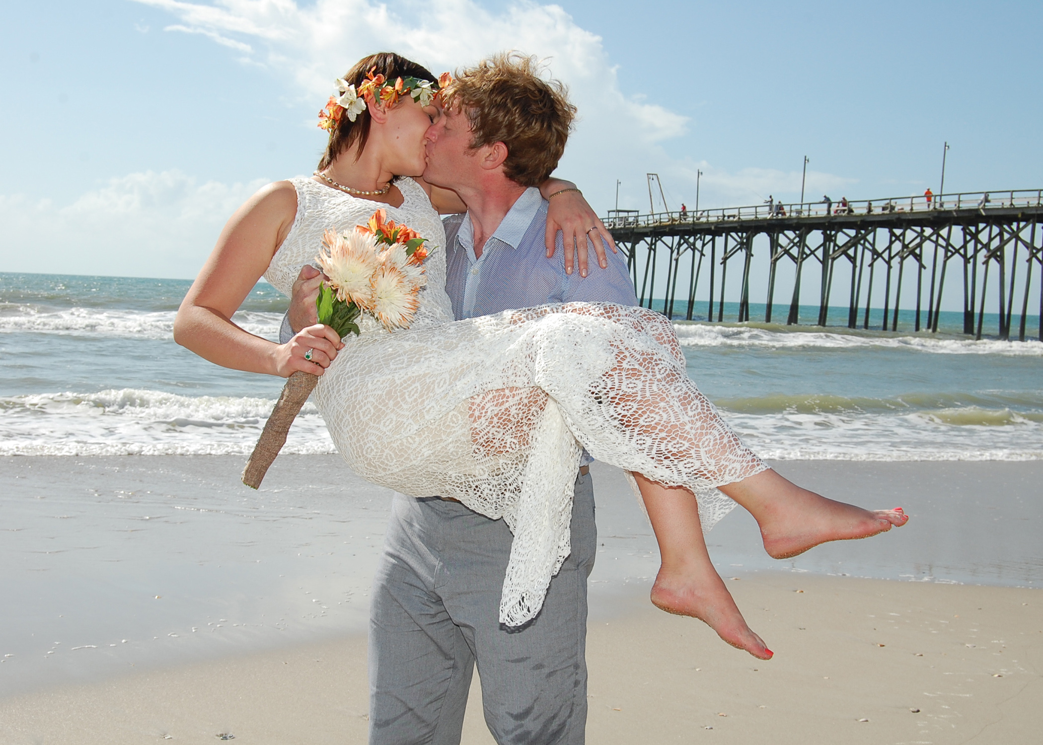 - Groom picks up his bride at the North end of Carolina Beach, NC. Fishing pier and ocean in the background. Bride is holding bouquet and wearing a flower Crown. Billy Beach Photography.