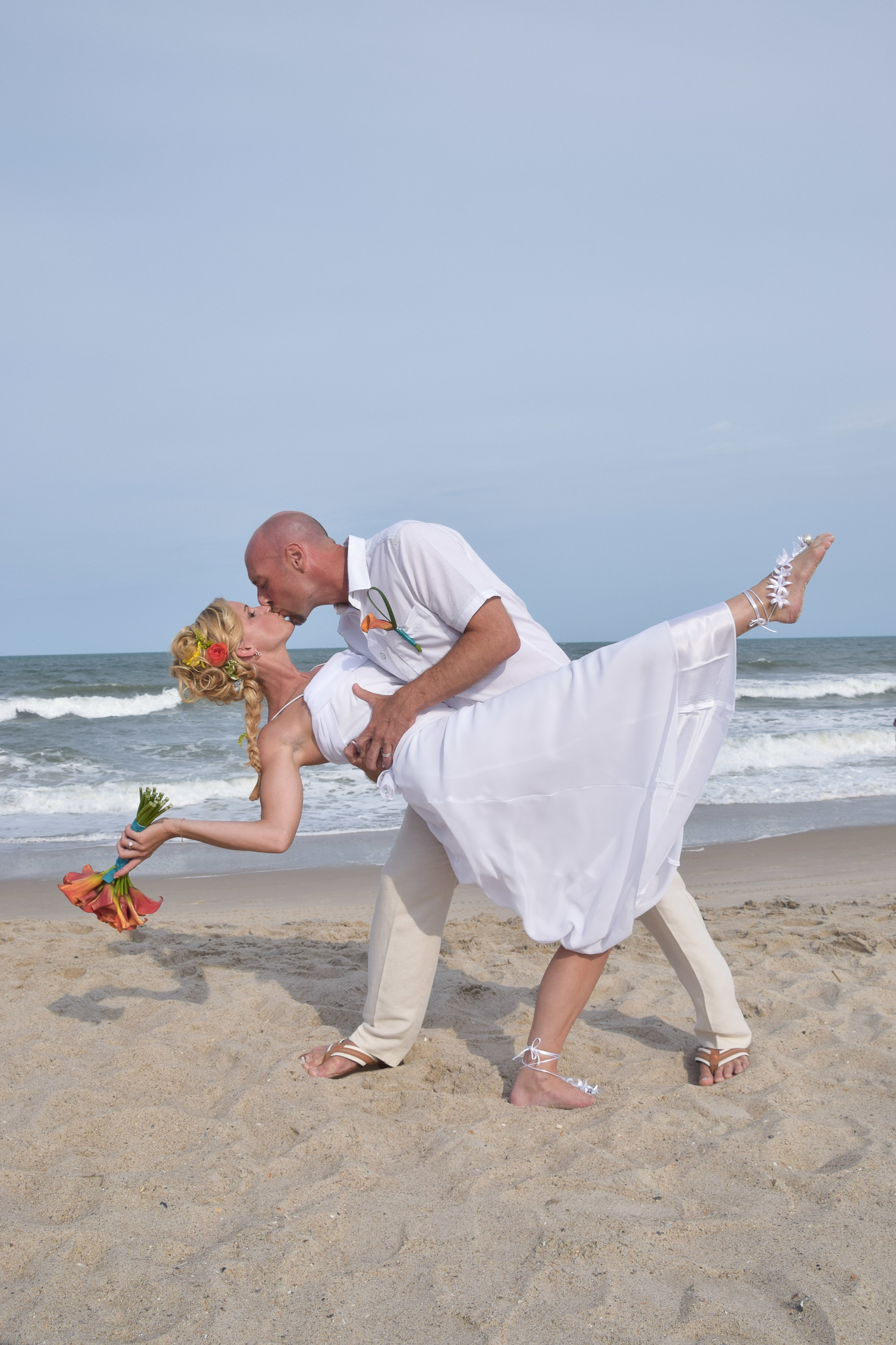 - Groom dipping his bride on Kure Beach, NC. Bride holding bouquet with flower in her hair. Ocean in the background. Billy Beach Photography.