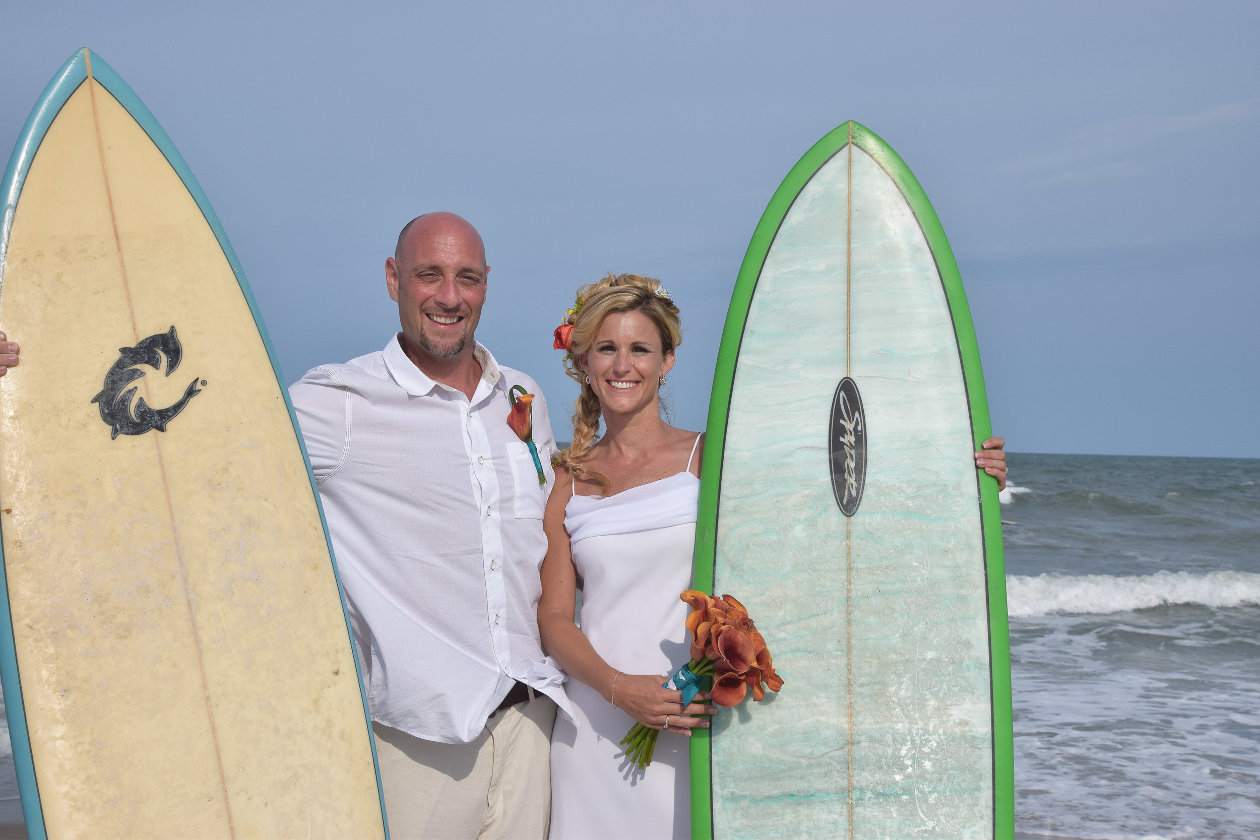 - Bride and groom posing with a couple of surf boards on Kure Beach, NC. We borrowed the boards from a couple of really nice random surfers to use as props. Ocean in the background. Billy Beach Photography.