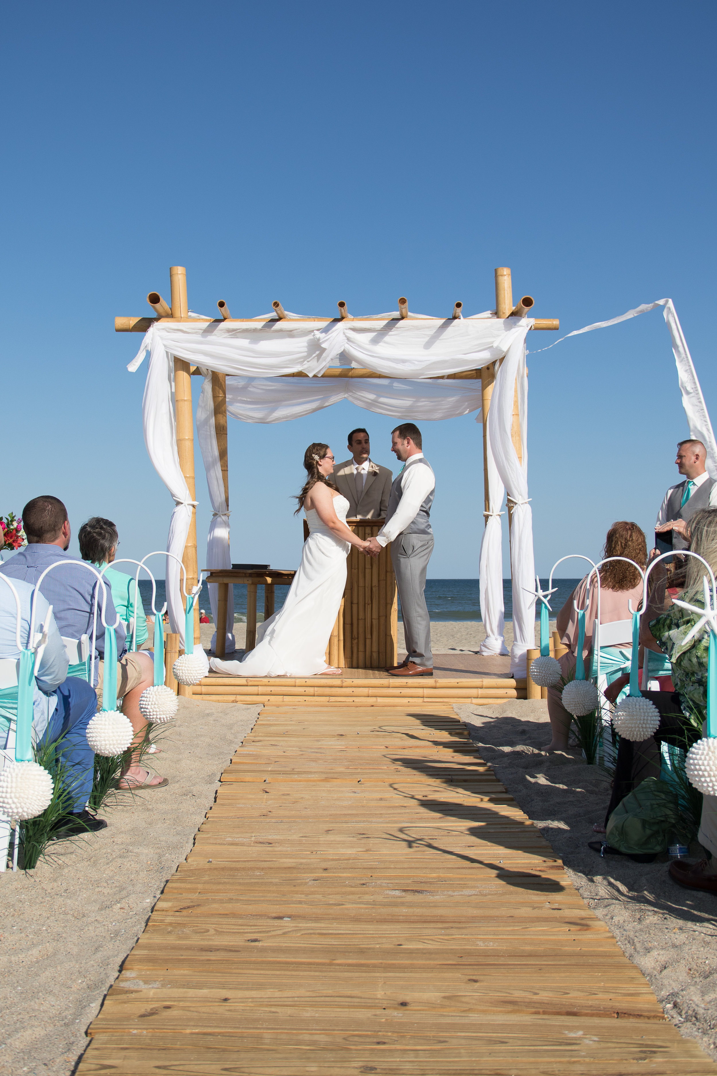 - Ceremony in progress at Fort Fisher, NC Bride and groom at alter while officiant conducts ceremony under a bamboo arbor, ocean in the background. Billy Beach Photography.