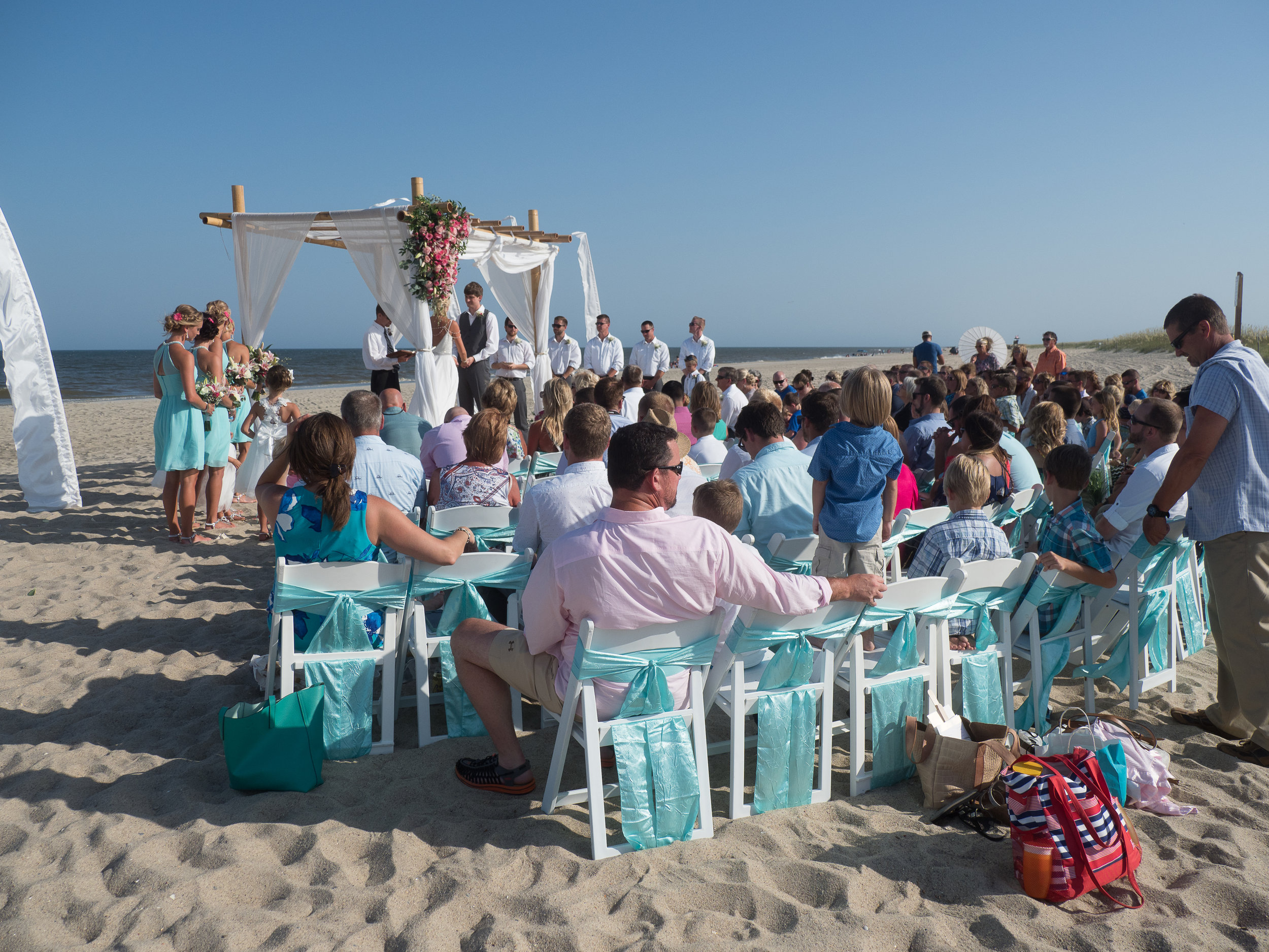 - Fort Fisher, NC beach ceremony in progress. Bride and groom under bamboo arbor and ocean in the background. Billy Beach Photography.