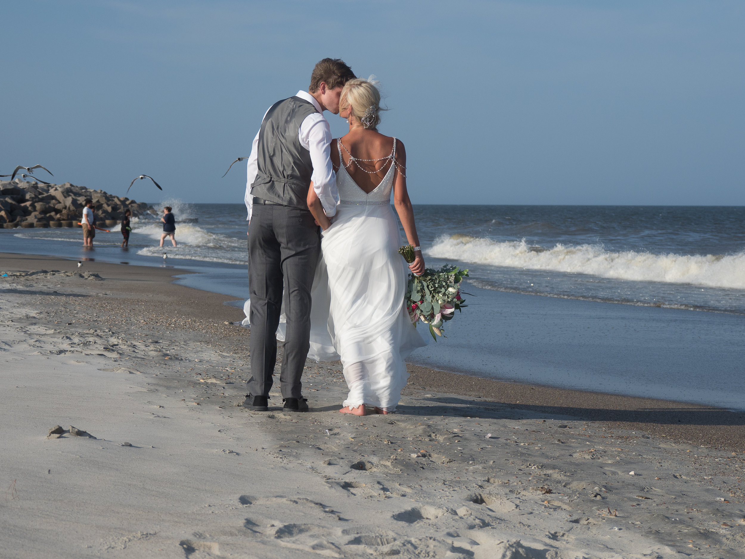 - Bride and groom walking on the beach stop for a quick kiss on Fort Fisher Beach, NC. Ocean in background with seagulls. Billy Beach Photography.