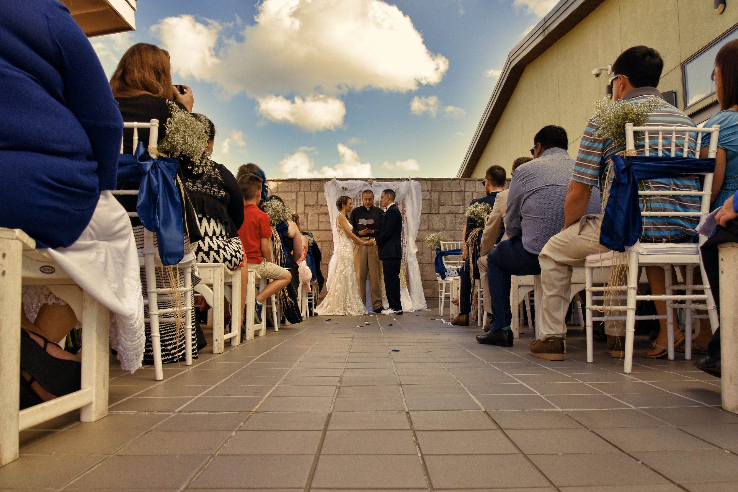 Vows. - Bride and groom reciting vows on the Terrace at Sir Tyler in Wilmington, NC.