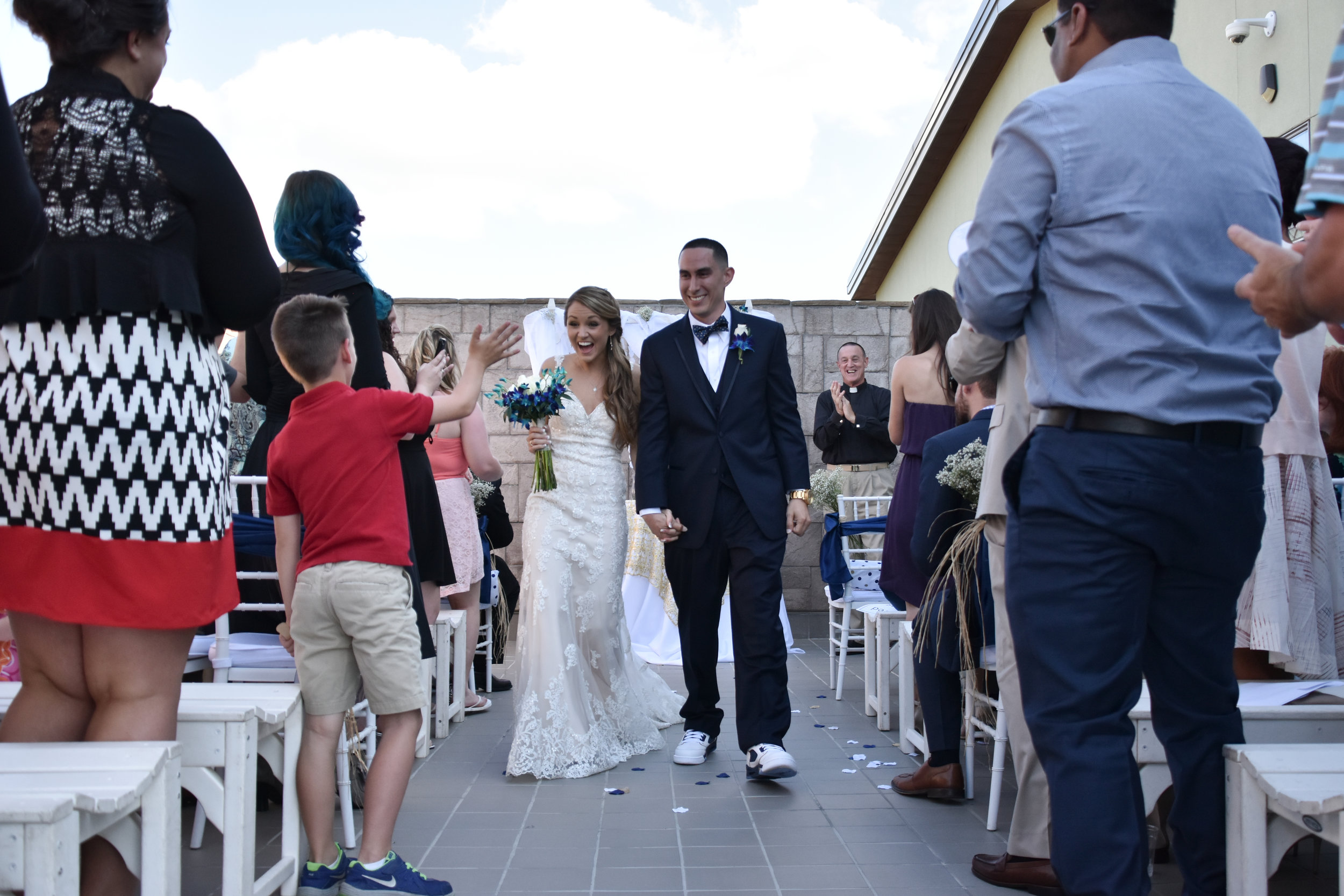 Egress. - Bride and groom walking up the aisle after the wedding ceremony at Terraces on Sir Tyler in Wilmington, NC.