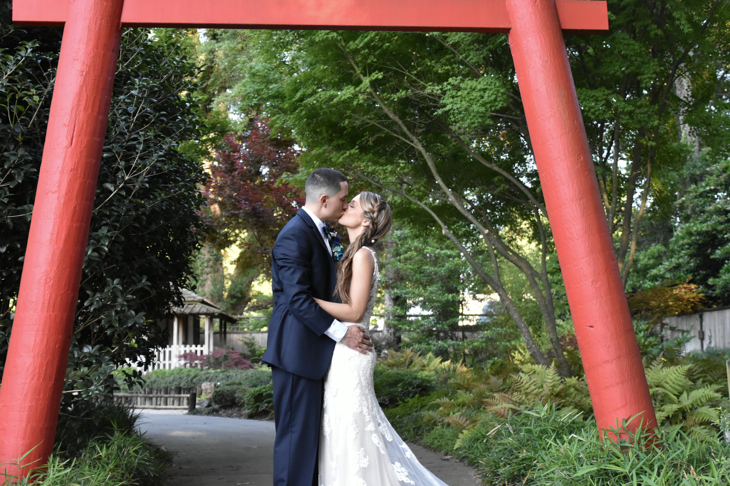 Torii - A kiss under the Torii gate at the Arboretum in Wilmington, NC. Japanese Tea House in background. Photos taken post ceremony at Terraces on Sir Tyler.