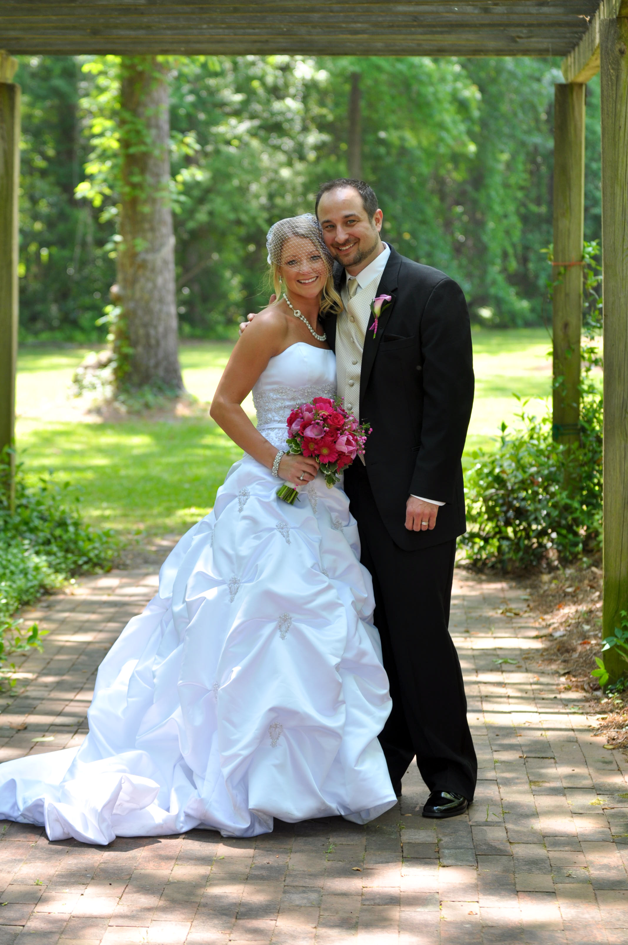 - Posed portrait of bride and groom at the Fragrance Garden, Greenfield Lake in Wilmington, NC. Billy Beach Photography. Affordable Wedding.