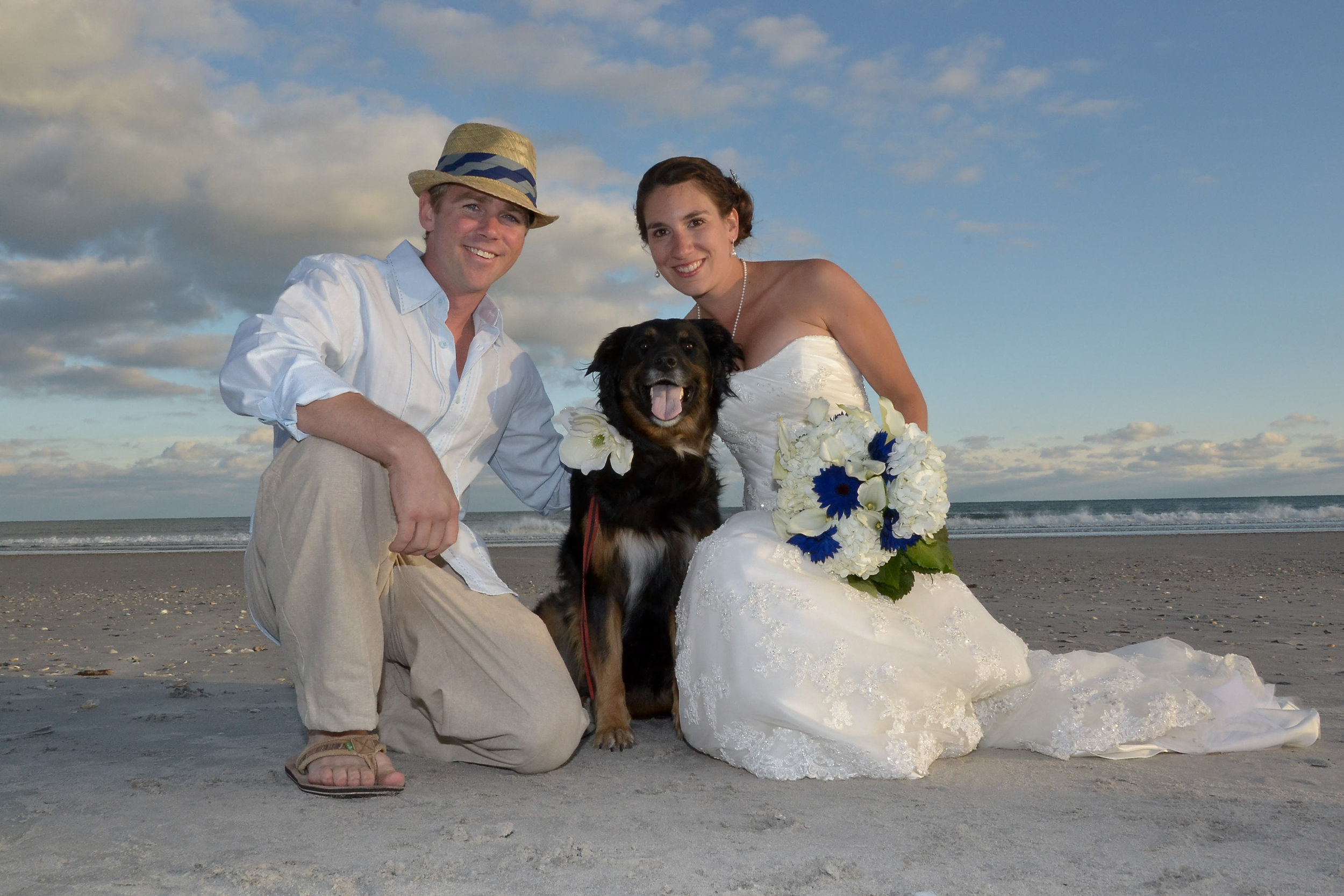 - Bride and groom posing with dog, on Topsail Beach, NC. Billy Beach Photography.
