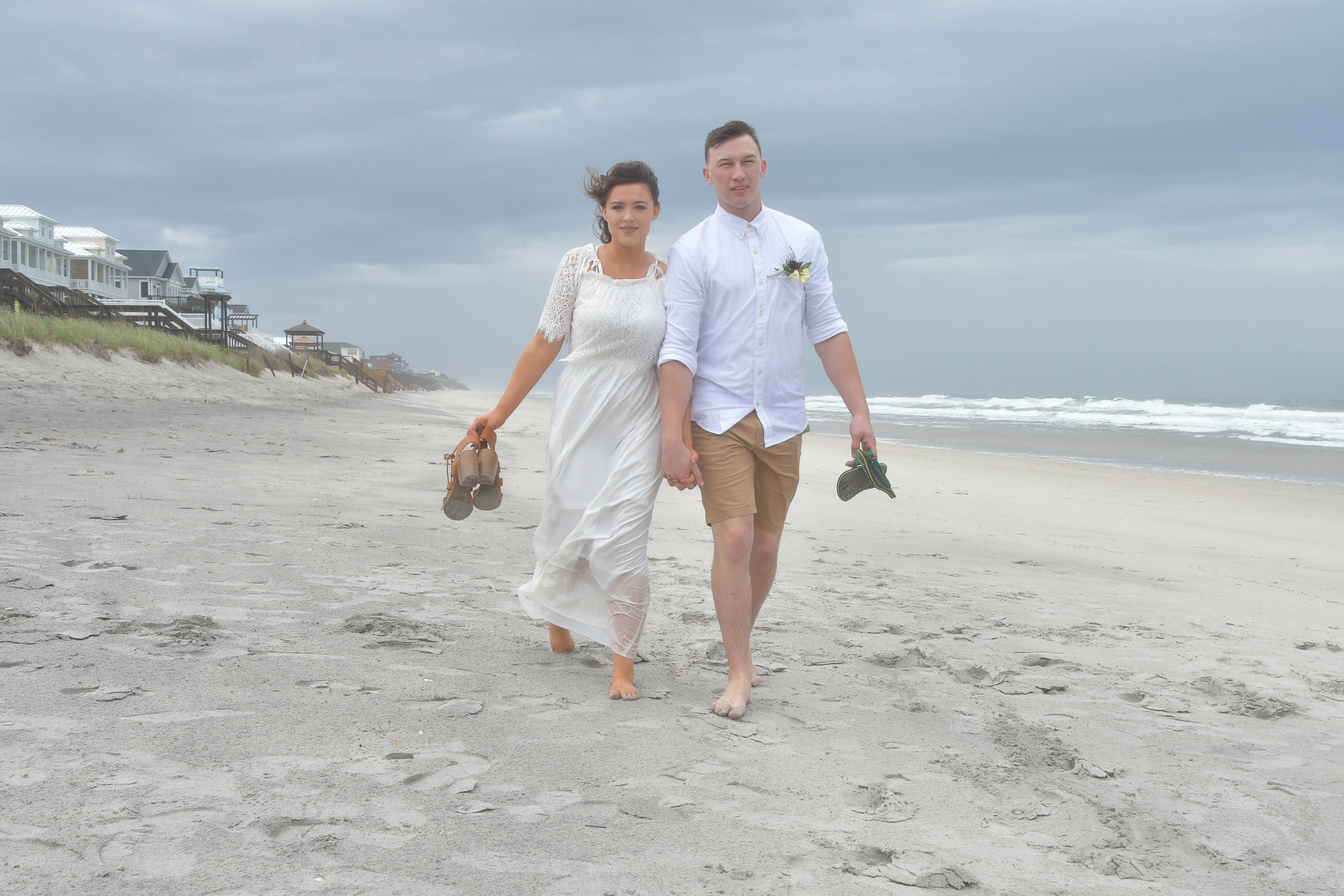 Shoes - Bride and groom walking down the beach carrying their shoes. Surf City, Topsail Island, NC. Billy Beach Photography.