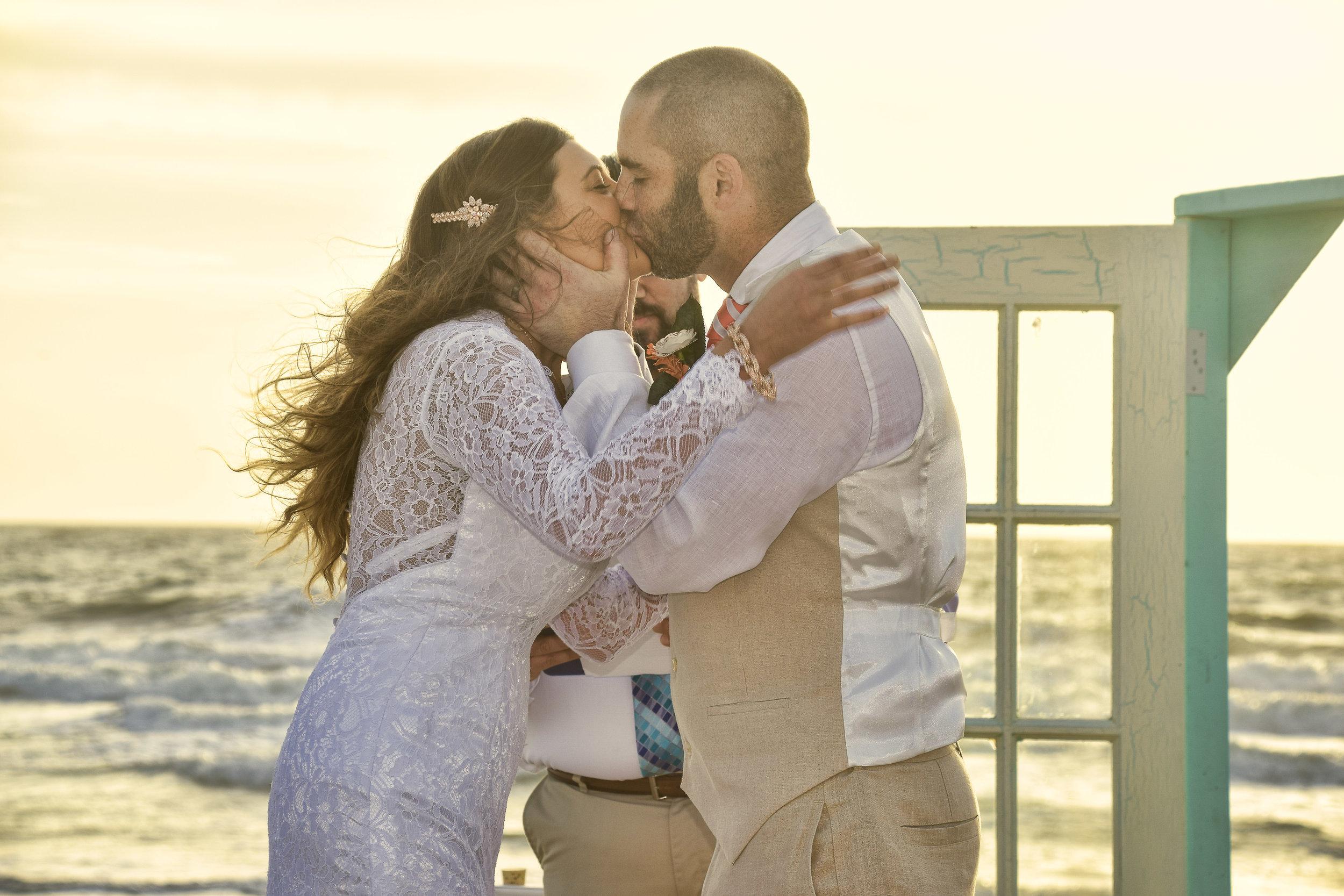 Kiss - First kiss at a sunrise wedding in Carolina Beach, NC. Billy Beach Photography.