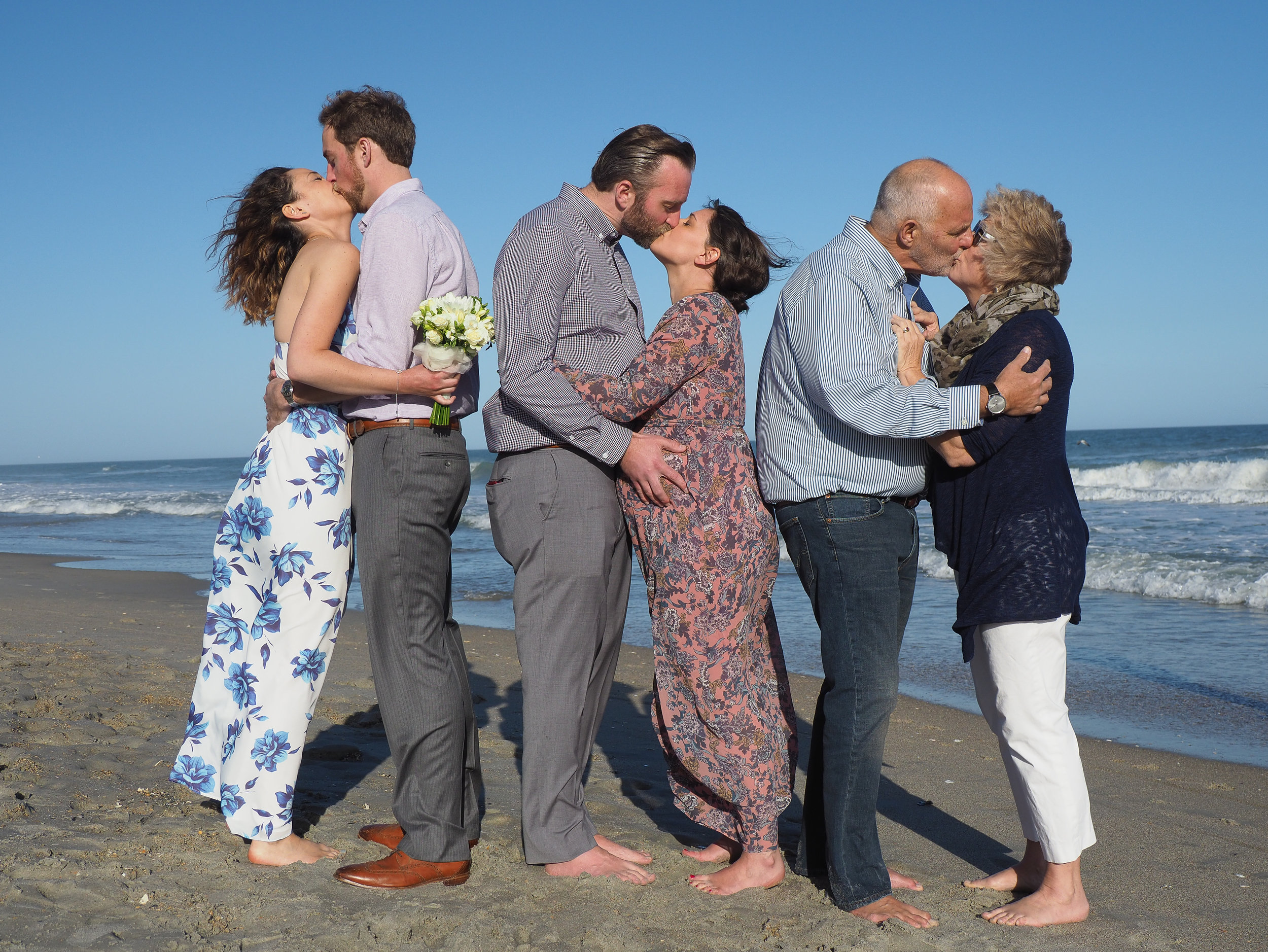 Group Kiss. All the married people share a kiss on the beach. Wrightsville Beach, NC.