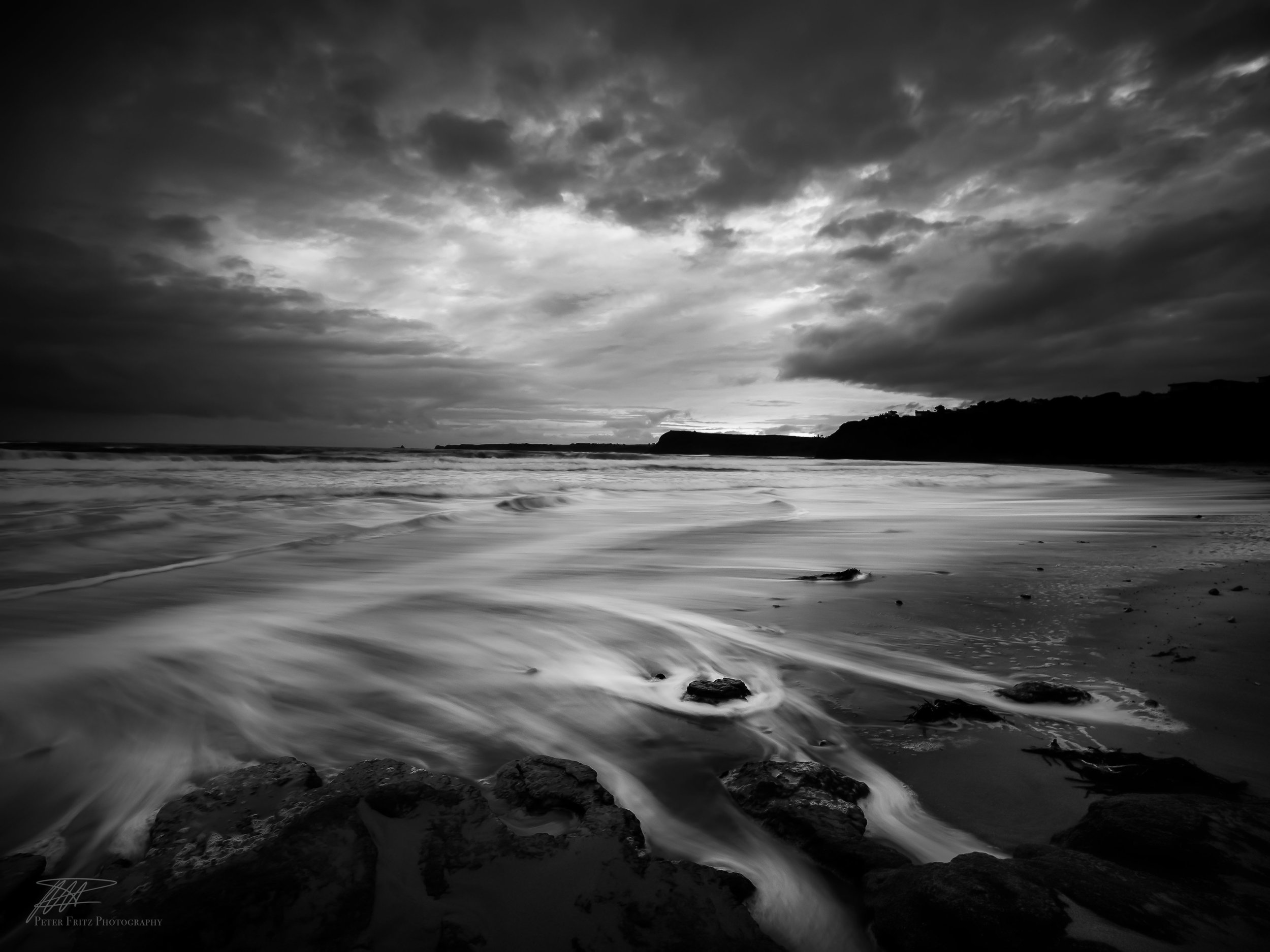 This BNW edit has made the clouds look more dramatic around the periphery of the sky allowing the light in middle to draw the views eyes to the centre of the image.