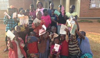 JC:HEM student conducts classes for children at the Dzaleka refugee camp, motivating others to follow her example and strive for higher education.