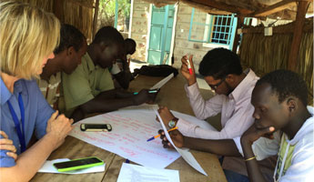 Mary McFarland participates in a brainstorming session with JC:HEM students in the Kakuma refugee camp in Kenya.