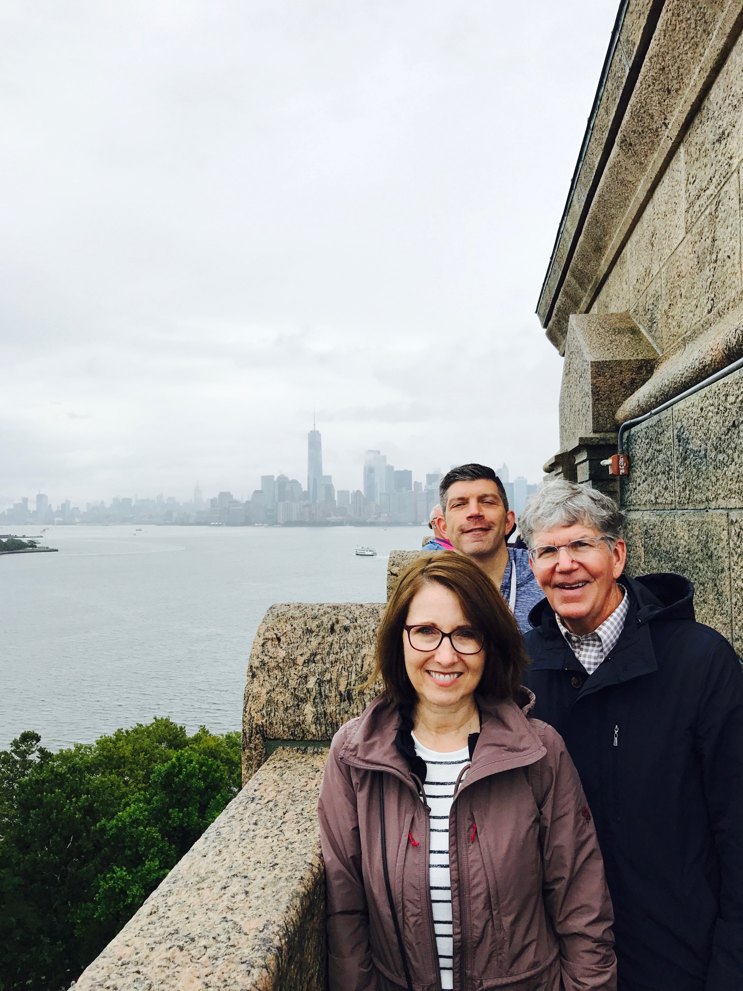Susan, John, and Fred with the NYC skyline in the background
