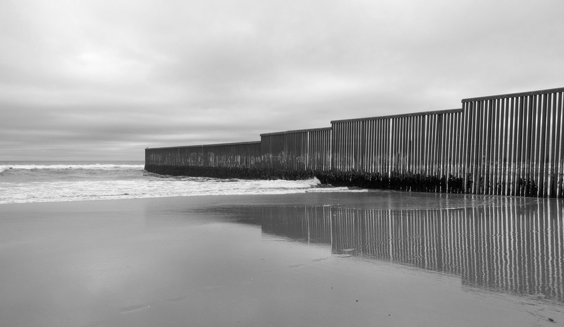 The border fence trails off into the Pacific Ocean.