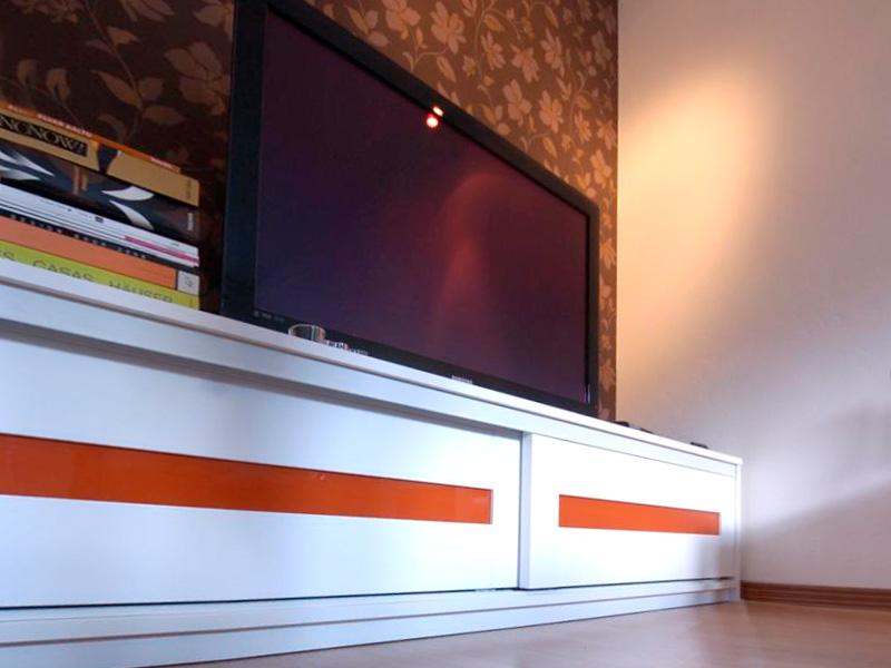 TV-taso Linear-liukuovilla, joissa oranssi lasi ja valkoiset kehykset.