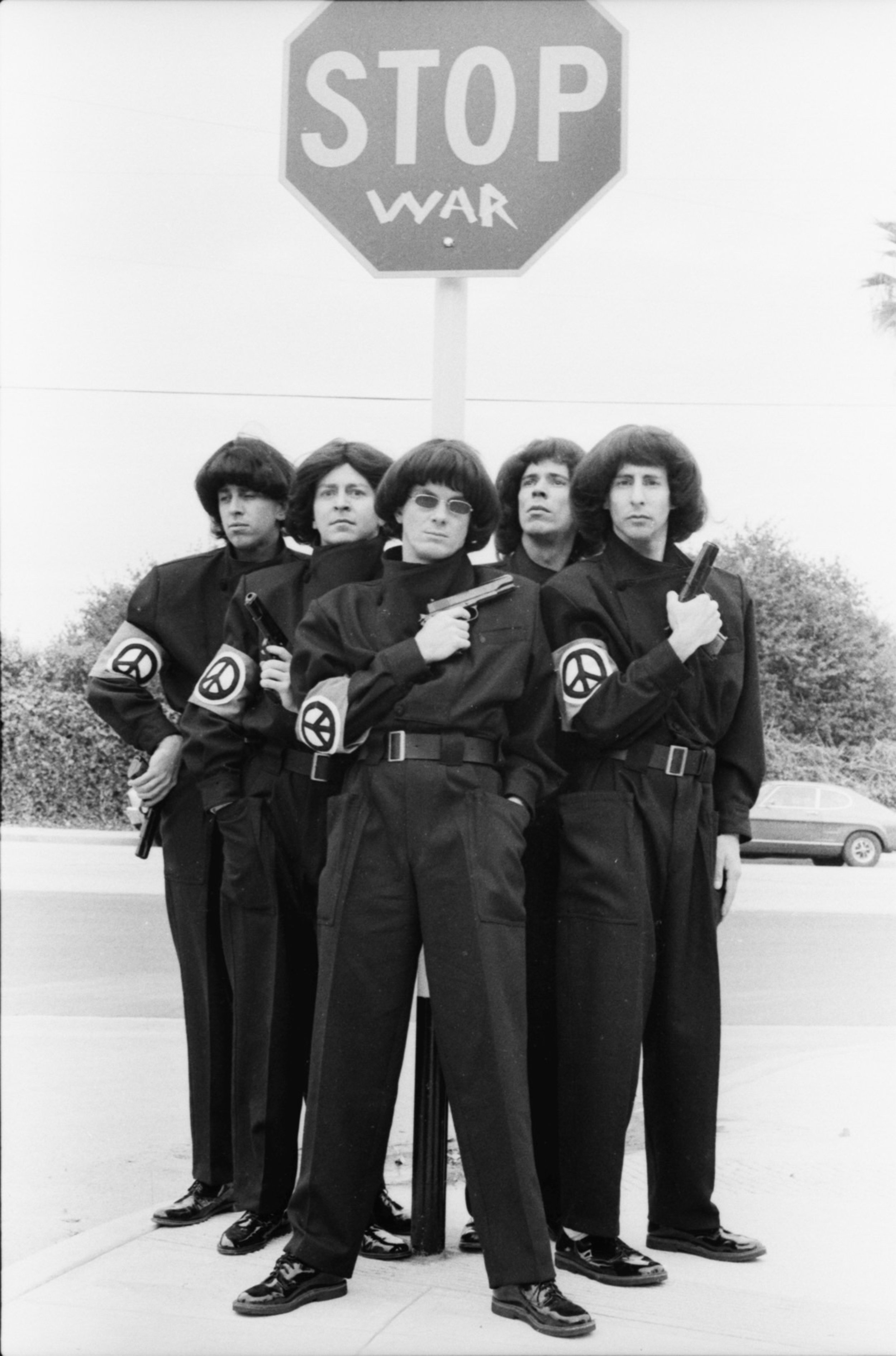 "Devo Stop War   ""While photographing DEVO on the street, they taped the word WAR below STOP, creating an iconic image."""