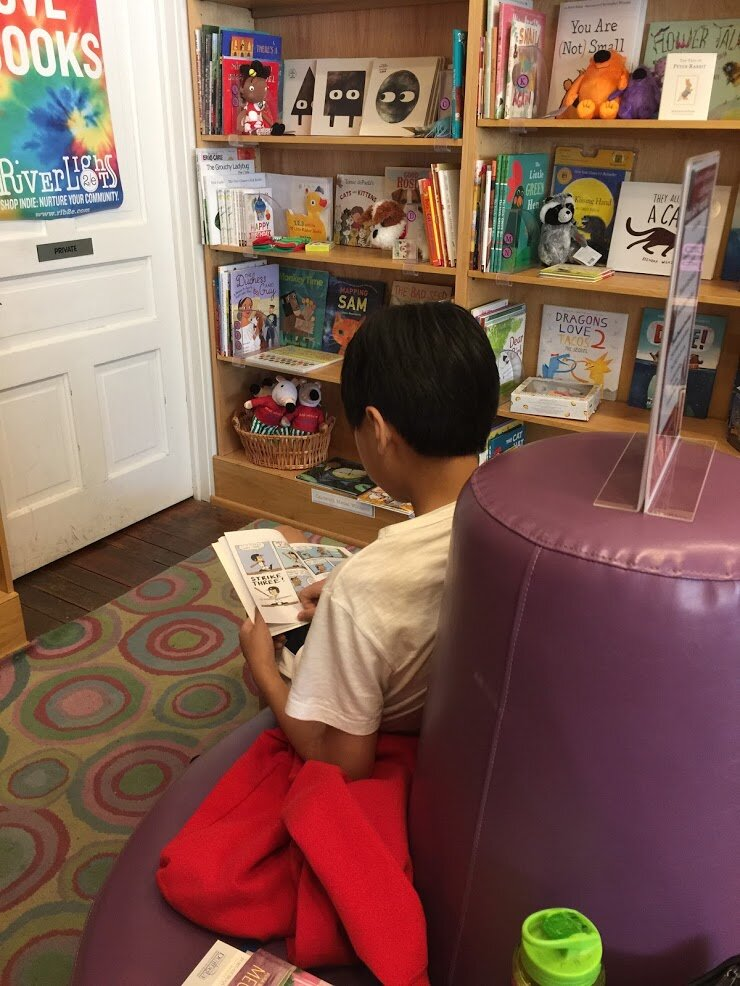 Liam reading in the heavenly children's book nook at the River Lights Bookstore in Dubuque, Iowa.