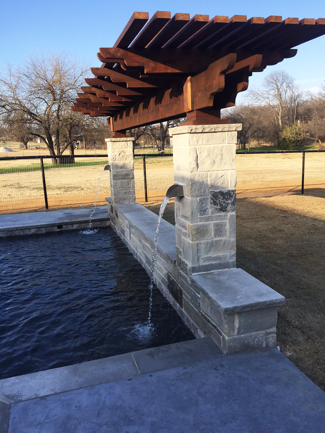 BMR pool and patio waterfall stone covered pergola.jpg