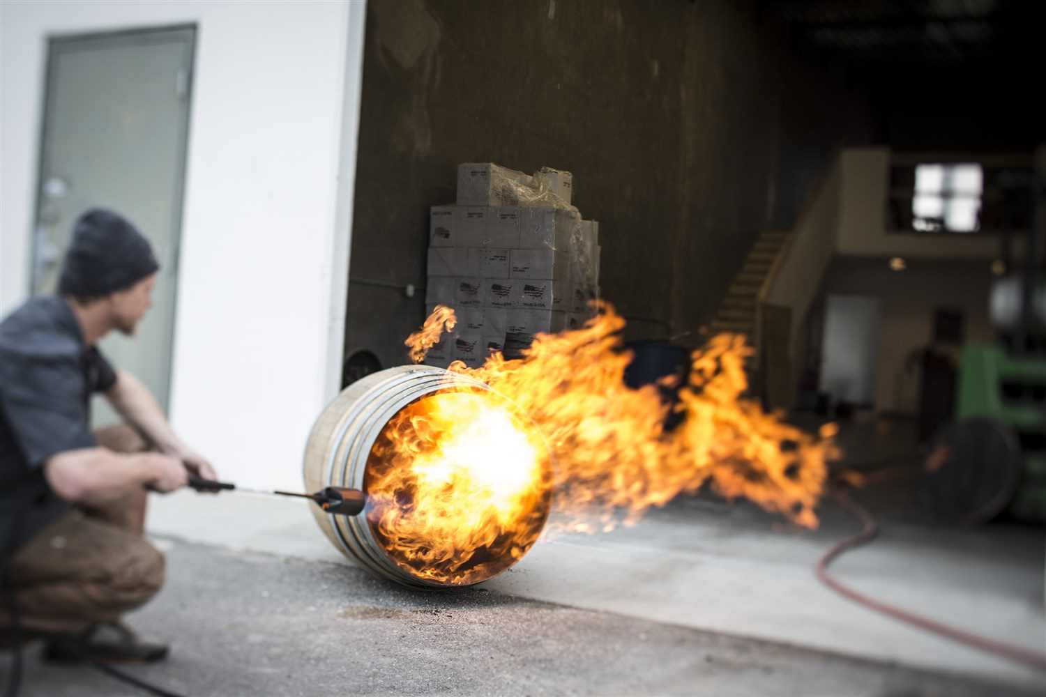 French Oak barrels previously used to cask wine (often chardonnay) are flame-charred with a tiger torch before being used to age gin.  Courtesy Beehive Distilling