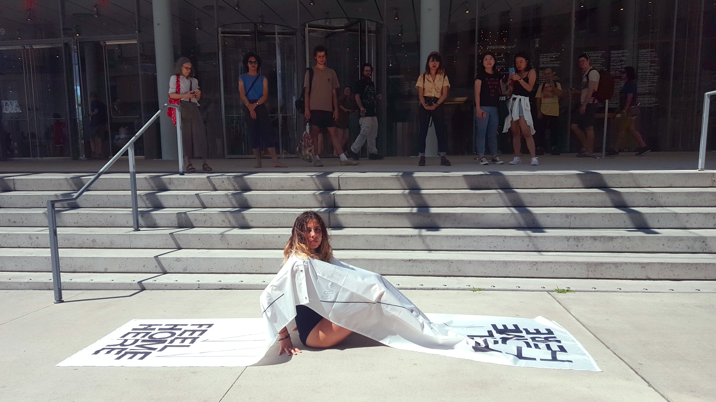 Feel Home Here; Feel Local Here, Feel New York Here. ( Performance at the entrance of the Whitney Museum of American Art, New York.2018) Lying on the Privately Owned Public Space sidewalk of the Whitney Museum