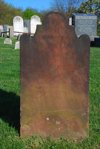"""This is an example of the oldest red sandstone markers in Bethel Cemetery. The rounded shape symbolized the """"doorway to heaven"""" and the """"hood of death."""" The stones are marvelous testimony to the creative skills of the talented artisans who carved them. Most of the men who cut gravestones were uninstructed craftsmen whose work was largely independent of formal principles of design. They worked alone in small villages, usually having another more profitable occupation such as blacksmithing, farming or fishing, receiving little or no attention for the unique work they did."""