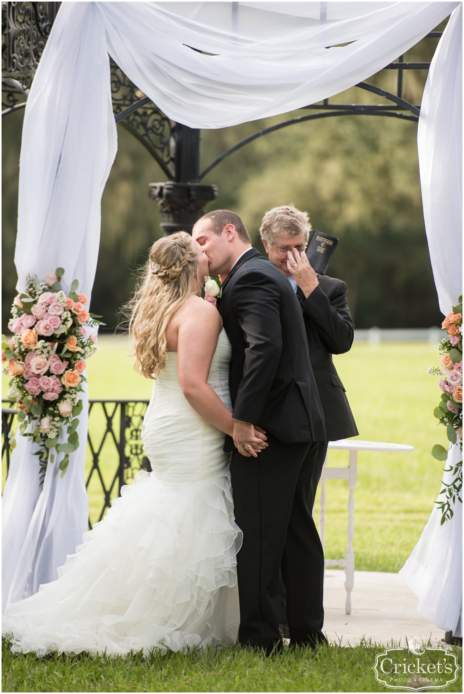 bride and groom kiss during their wedding ceremony