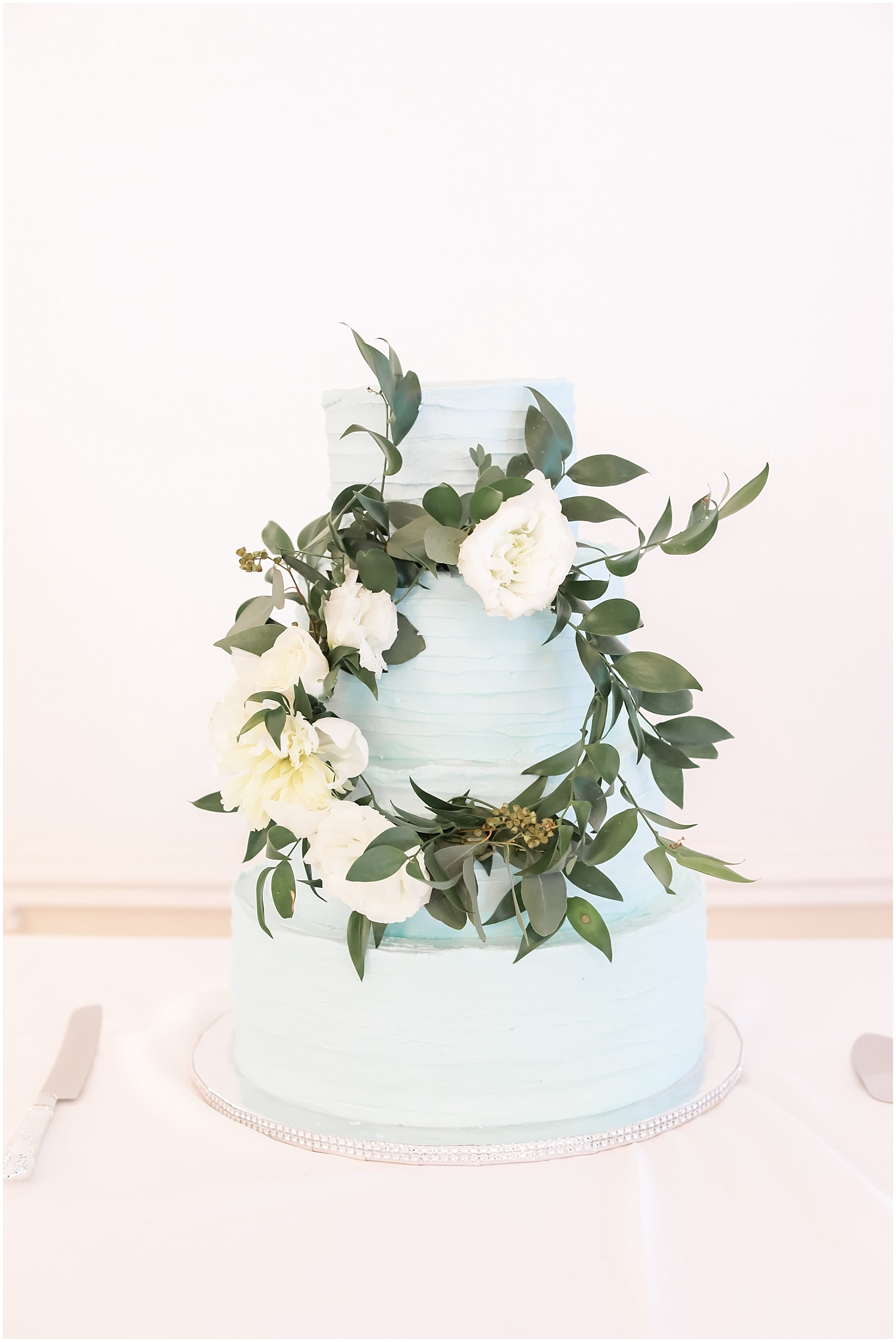 baby blue wedding cake with greenery decor
