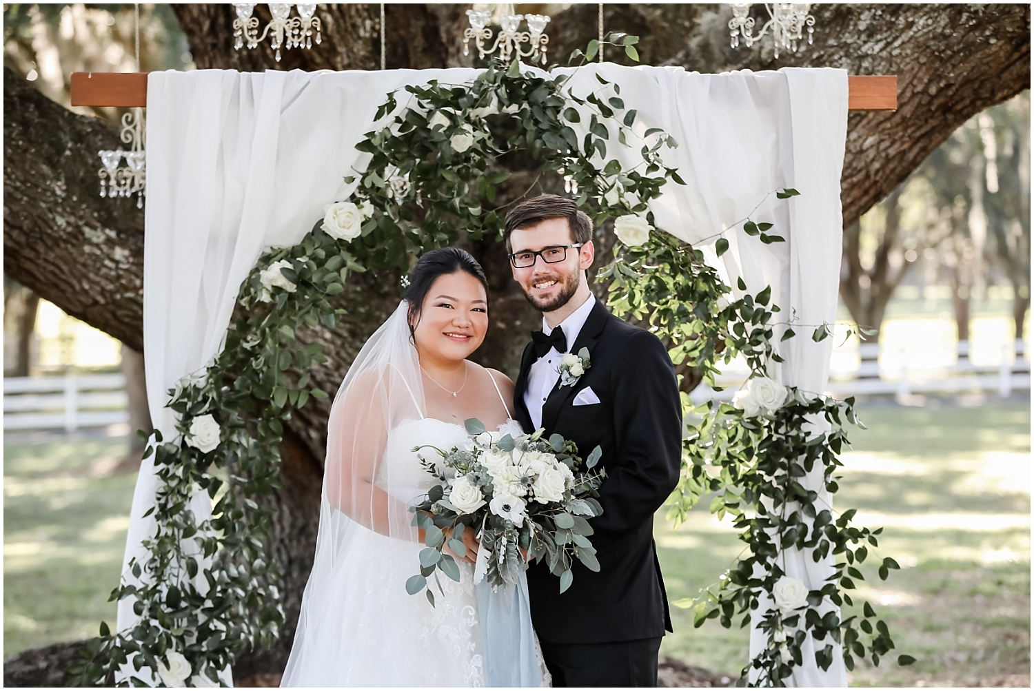 bride and groom portrait with their wedding arch