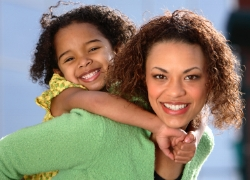 Girl piggy-backing on mom; treat developmental delays at Canto Speech Therapy Online