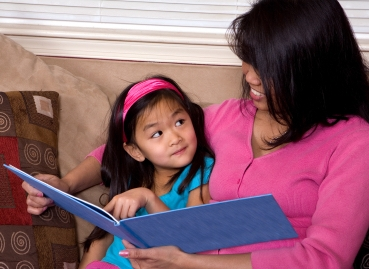 Mom and little girl reading a book; strong rhyming and  phonological awareness skills improve reading success.  Learn more at Canto Speech Therapy Online