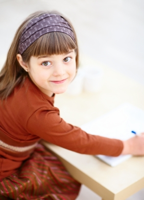 Little girl writing.  Learn how kids learn to read at Canto Speech Therapy Online
