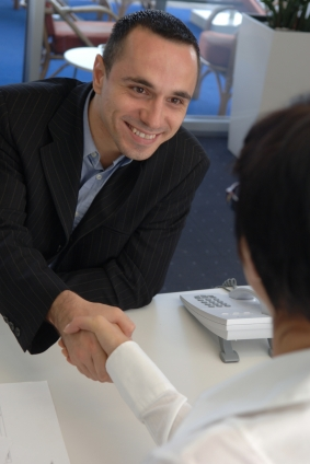 Businessman shaking hands securing deal; improve English accent at Canto Accent Management at correctmyaccent.com