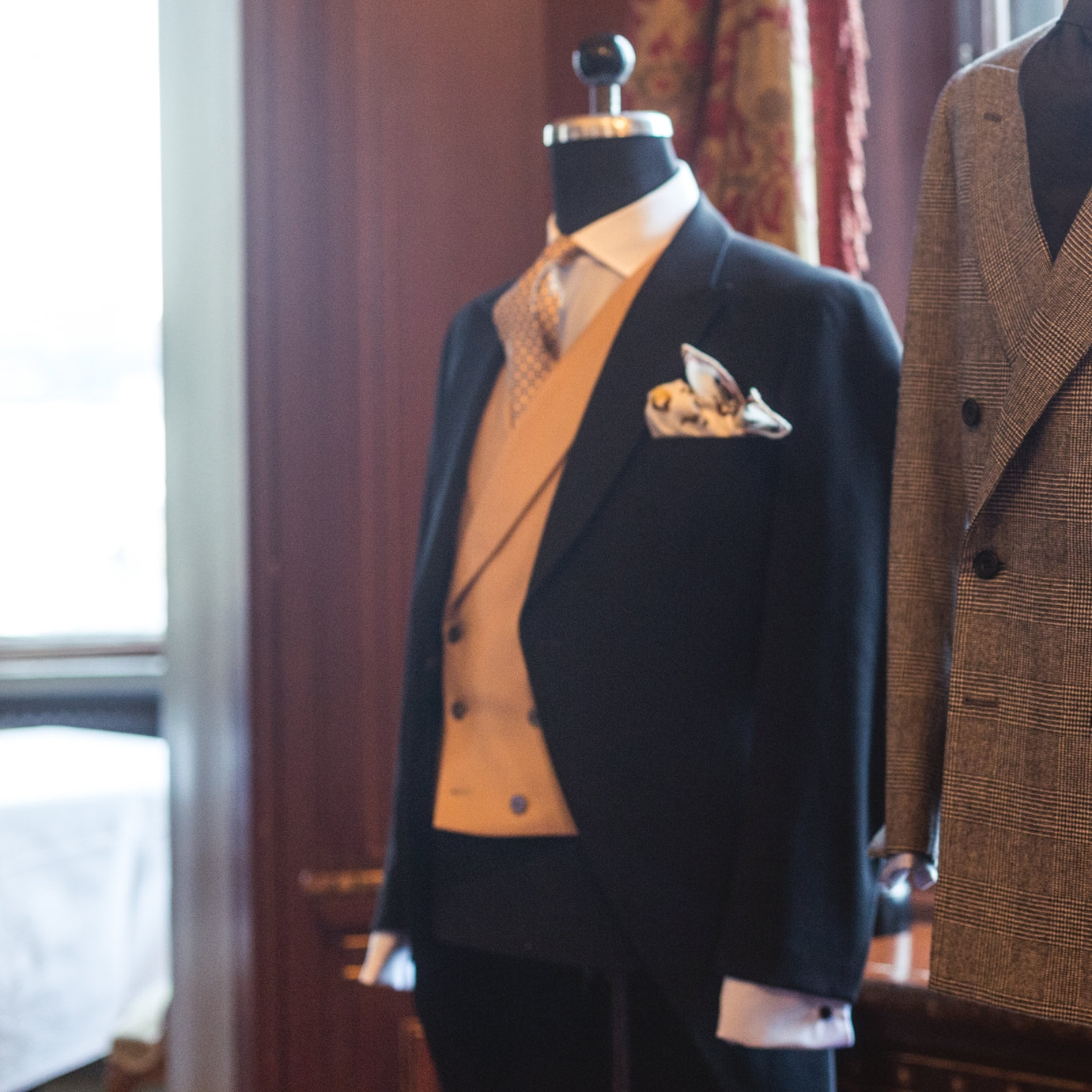 Black wool morning coat with blue shirt, tan waistcoat and yellow tie.