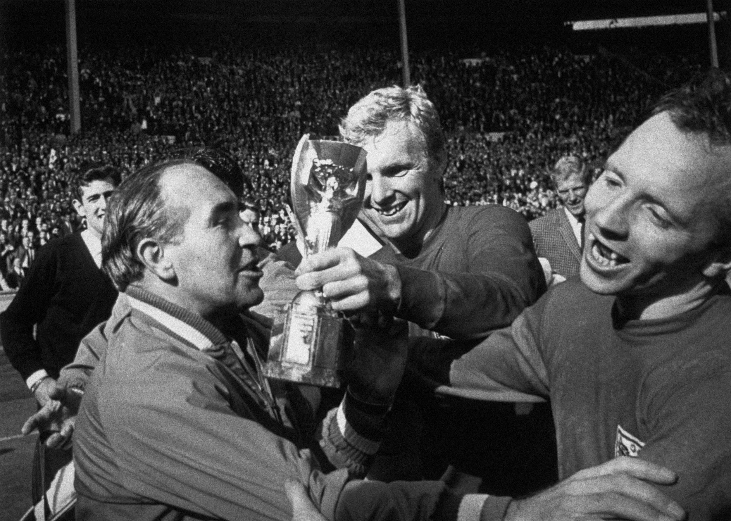 Celebrations following England's win over West Germany in the 1966 World Cup held at Wembley. The England captain, Bobby Moore, holds the Jules Rimmet Cup which the team manager, Alf Ramsay is about to kiss. A delighted Nobby Stiles is also shown.  Photo by Hulton-Deutsch/Hulton-Deutsch Collection/Corbis via Getty Images.