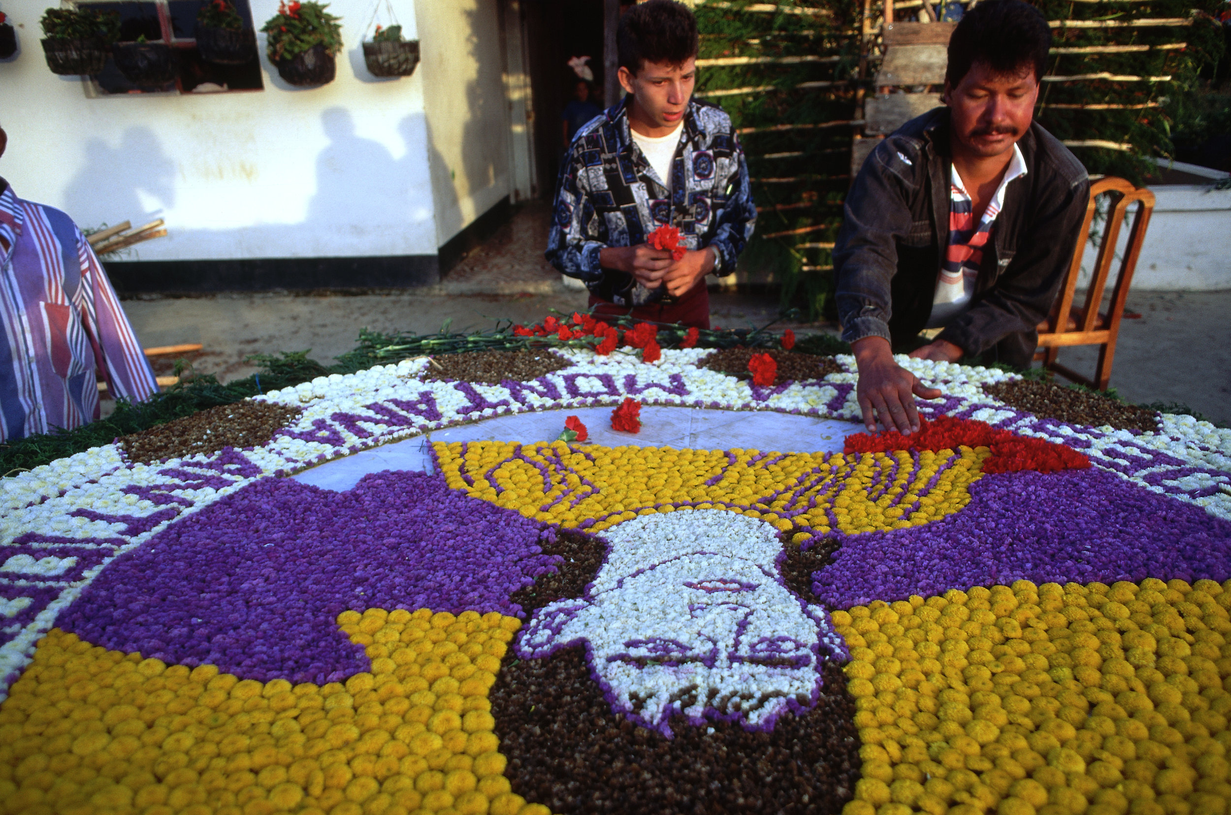 Two men construct a flower memorial to Andrés Escobar. Photo by Jeremy Horner/Corbis.