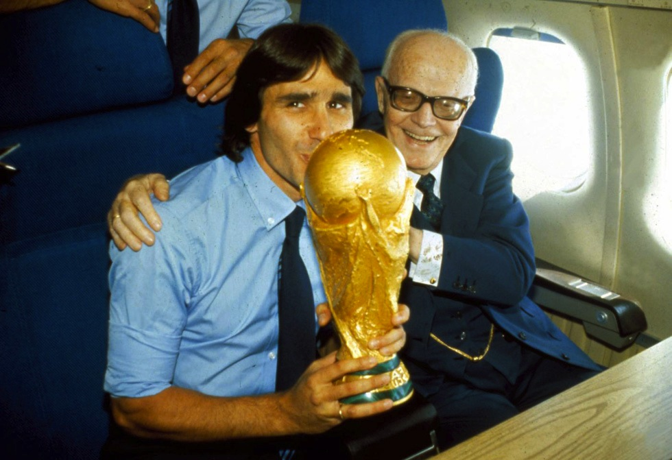 Bruno Conti kisses Italy's 1982 World Cup trophy on his flight home from Spain with then-president of the Italian Republic, Sandro Pertini.