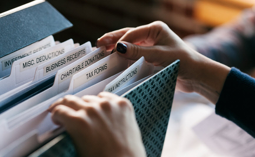 woman-digging-through-tax-file-folder-for-receipts_INF31425.jpg