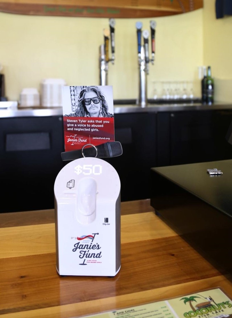 """Janie's Fund and DipJar - Steven Tyler's Janie's Fund is partnering with Maui restaurants to collect donations through DipJar:""""We are excited to have Coconut's become our first official partner using DipJars to raise funds for our important work that's directly supporting girls and young women that have experienced abuse and neglect.-Richard Shaw, Janie's FundMichael Phillips, the CEO and founder of the restaurant chain, is excited for the partnership as well:""""So many people visit our restaurants each day. Coconut's will help deliver a broader support network for Janie's Fund, and these new self-service donation stations will enable customers to contribute in just seconds.""""-Michael Phillips, Coconut's"""