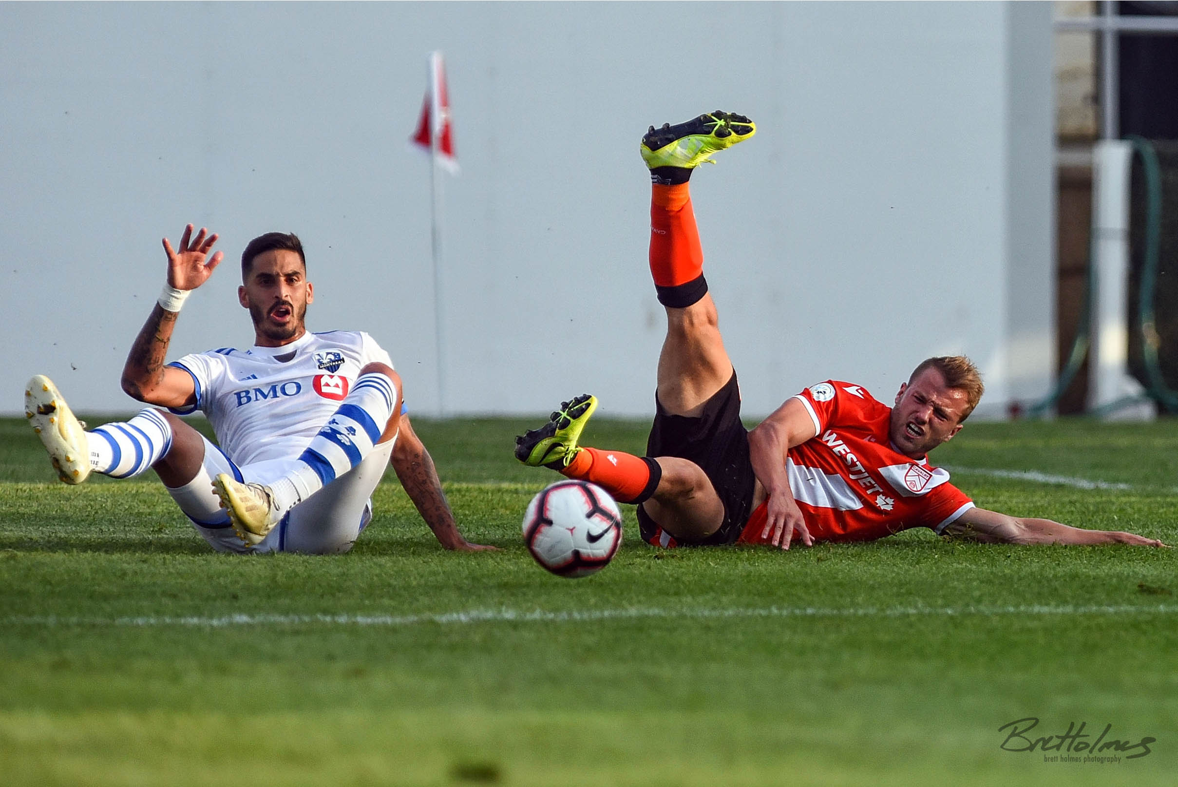 CALGARY, AB - AUGUST 14: Cavalry FC midfielder Julian Büscher (8) is taken down by Montreal Impact defender Jorge Corrales (26) during the first half of the second leg of a Canadian Championship semifinal match between the Montreal Impact and Cavalry FC on August 14, 2019, at ATCO Field at Spruce Meadows in Calgary, AB. (Photo by Brett Holmes/Icon Sportswire)